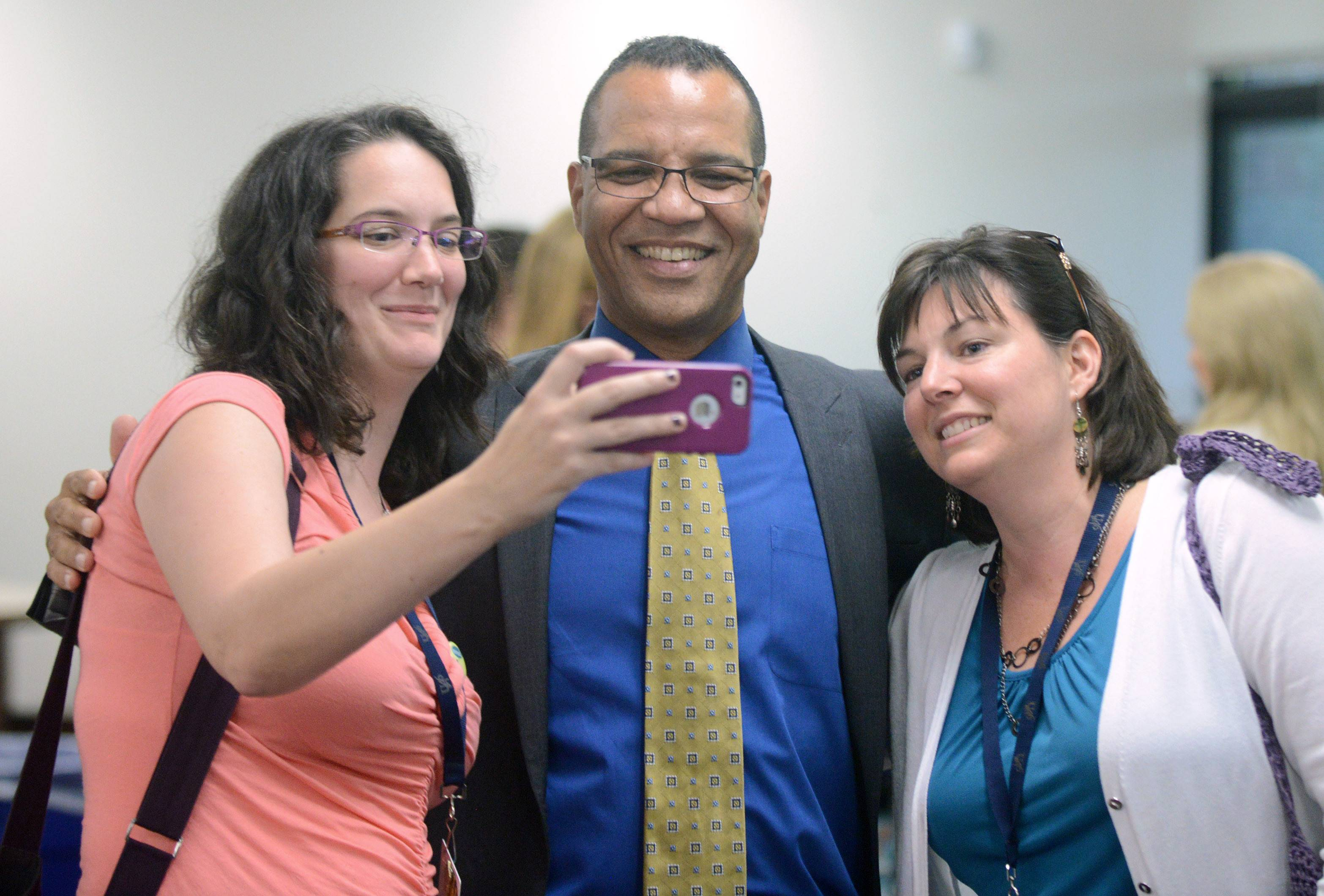 Transformation coaches Erin Jackle, left, and Angie Gallegos take a 'selfie' Friday with Elgin Area School District U-46 Superintendent Jose Torres at his farewell reception at the Elgin High School library.