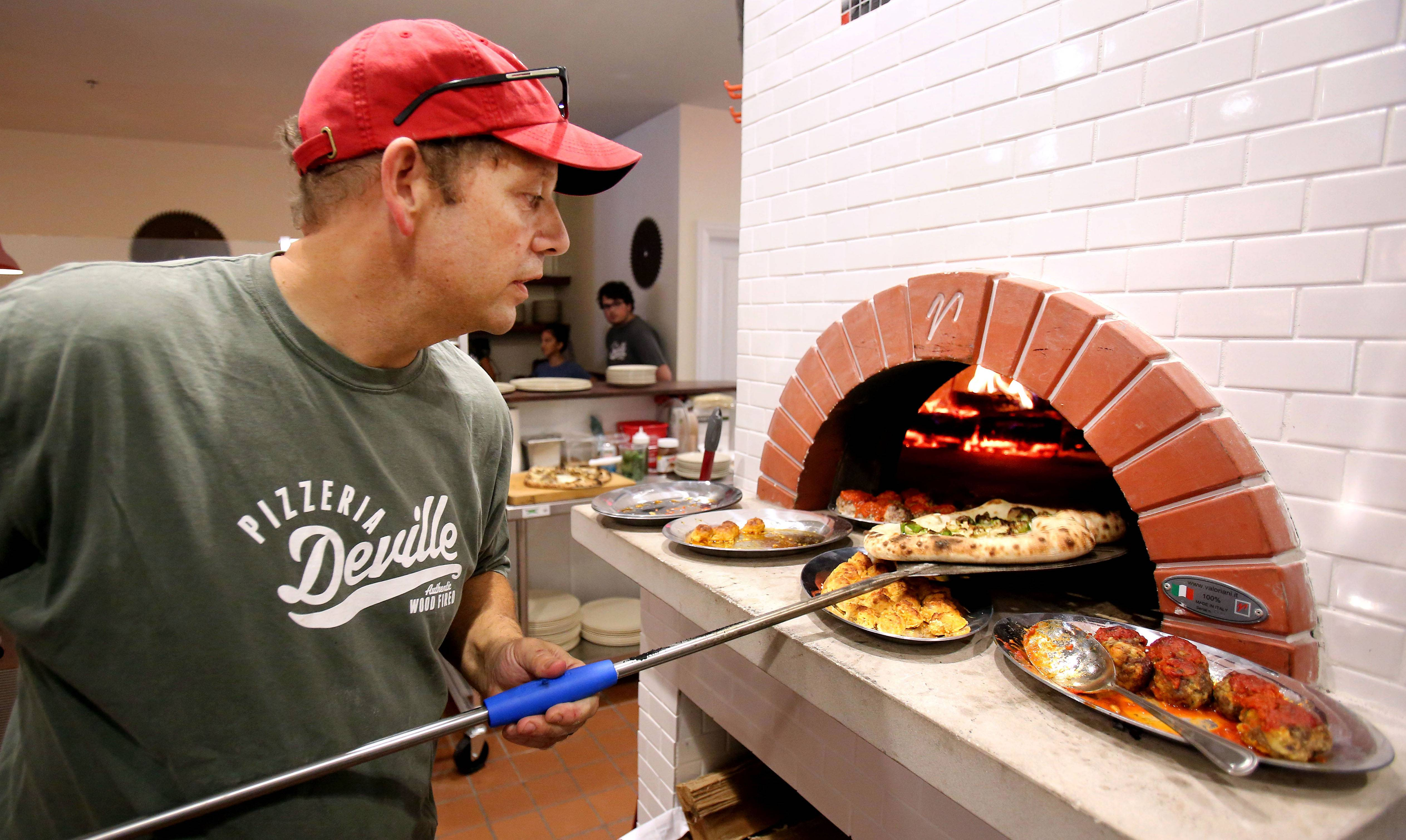 John Durning carefully pulls a pizza from the wood-fired oven during a tasting for his new restaurant Pizzeria DeVille in Libertyville.