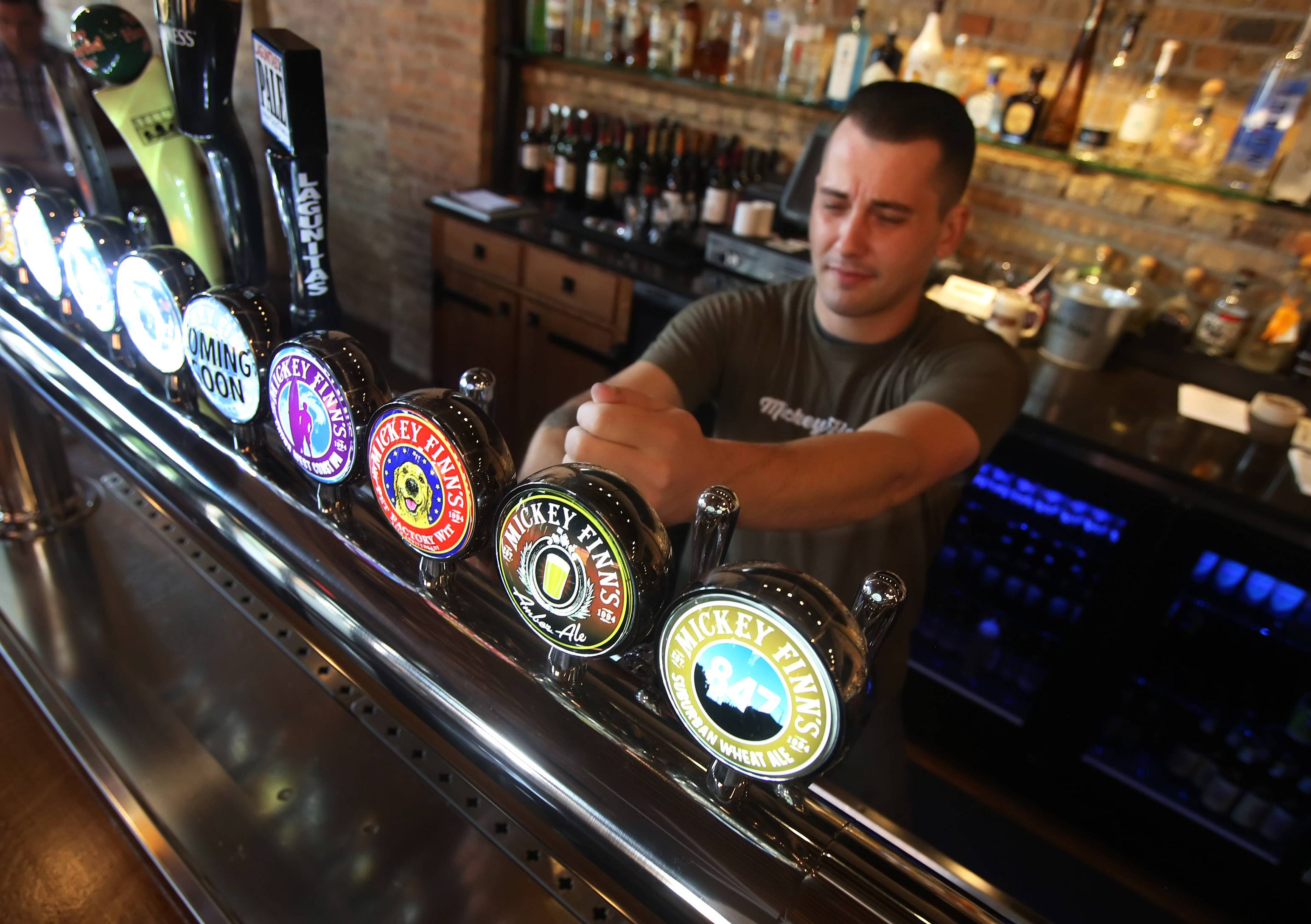 Bartender Patrick McLaughlin pours a beer at Mickey Finn's in Libertyville.