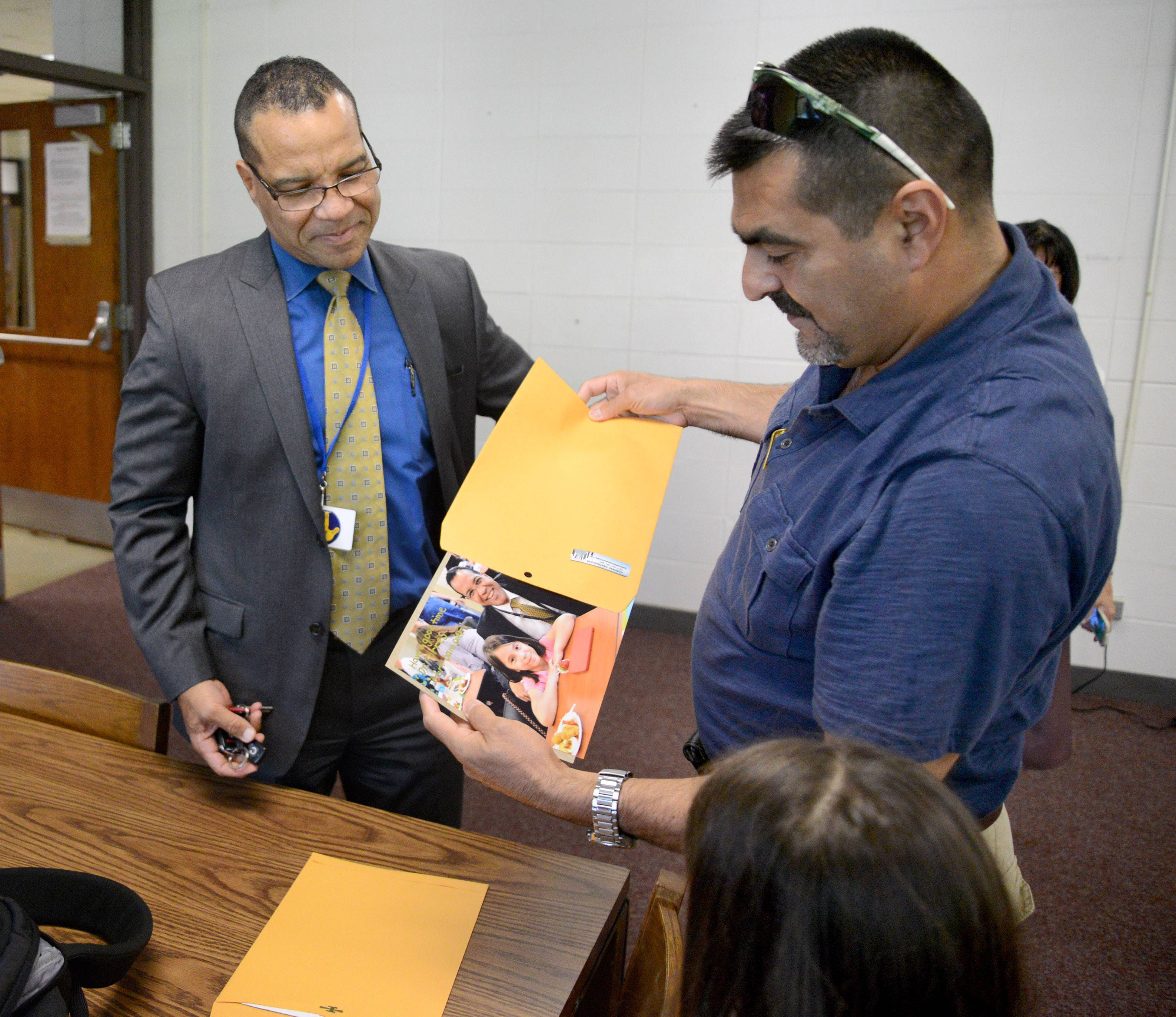 Guillermo Sampieri of Elgin pulls out a photo taken last May with Elgin Area School District U-46 Superintendent Jose Torres and his daughter, Abrianna, 8, right, for Torres to sign for her at his farewell reception. Sampieri brought a second copy for Torres to keep.