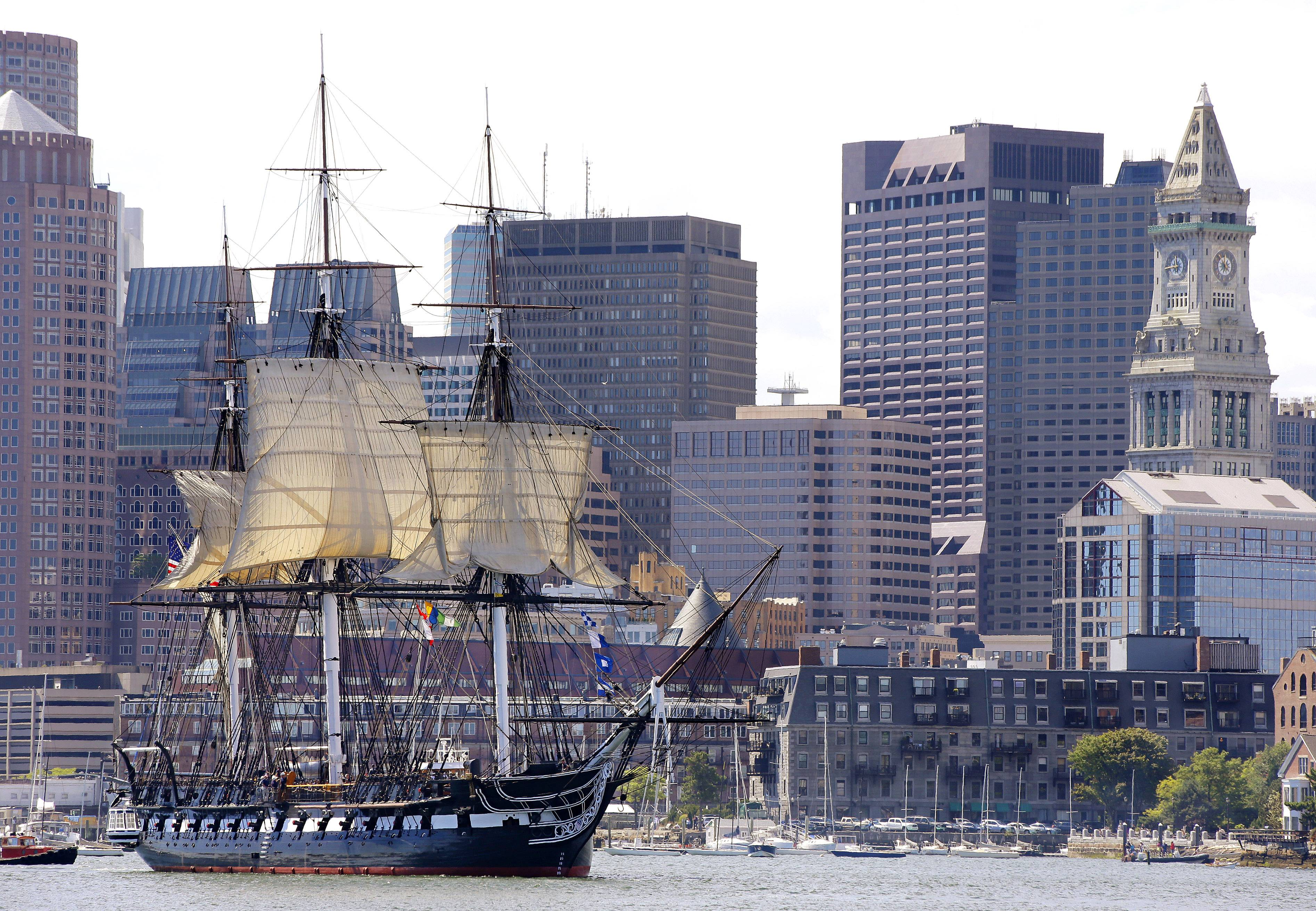 "The U.S.S. Constitution, or ""Old Ironsides,"" the U.S. Navy's oldest commissioned ship that is still afloat, is towed Friday through Boston Harbor past the financial district skyline with its topsails unfurled."