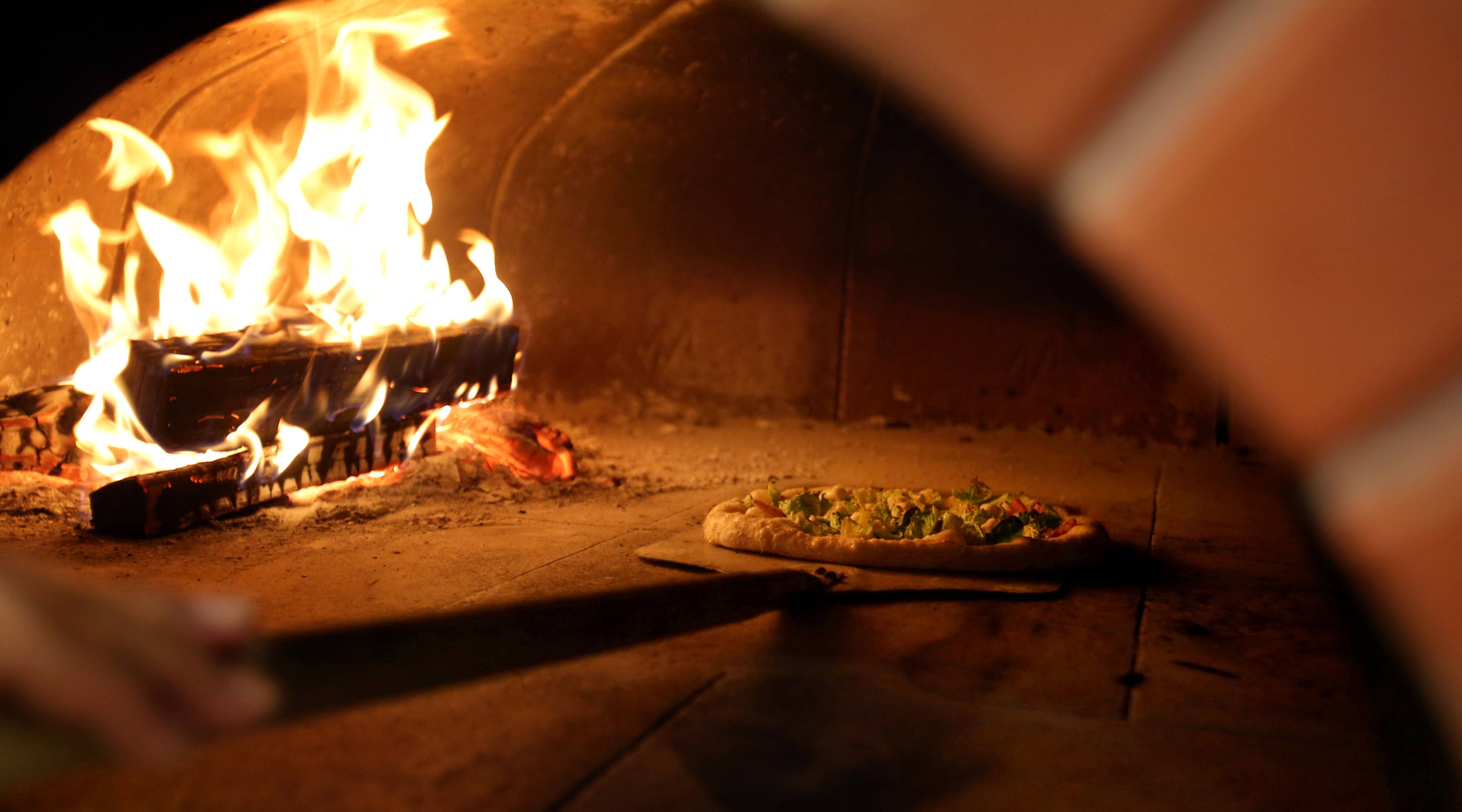 John Durning uses a wood-fired oven that can reach 900 degrees to make pizza at his new Pizzeria DeVille in Libertyville.