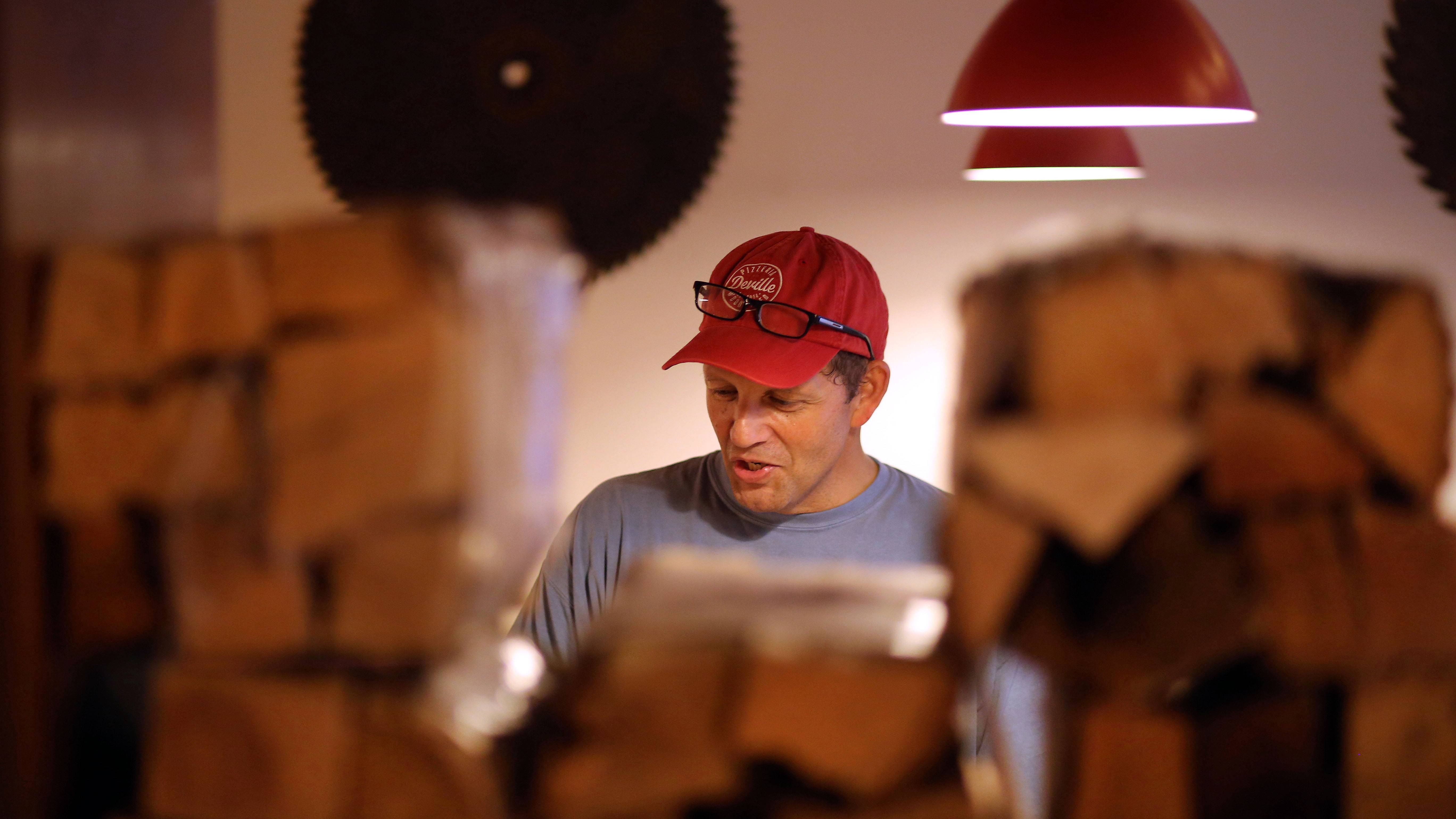 John Durning is framed by the wood he uses for his oven as he talks with customers at his new restaurant Pizzeria DeVille in Libertyville.