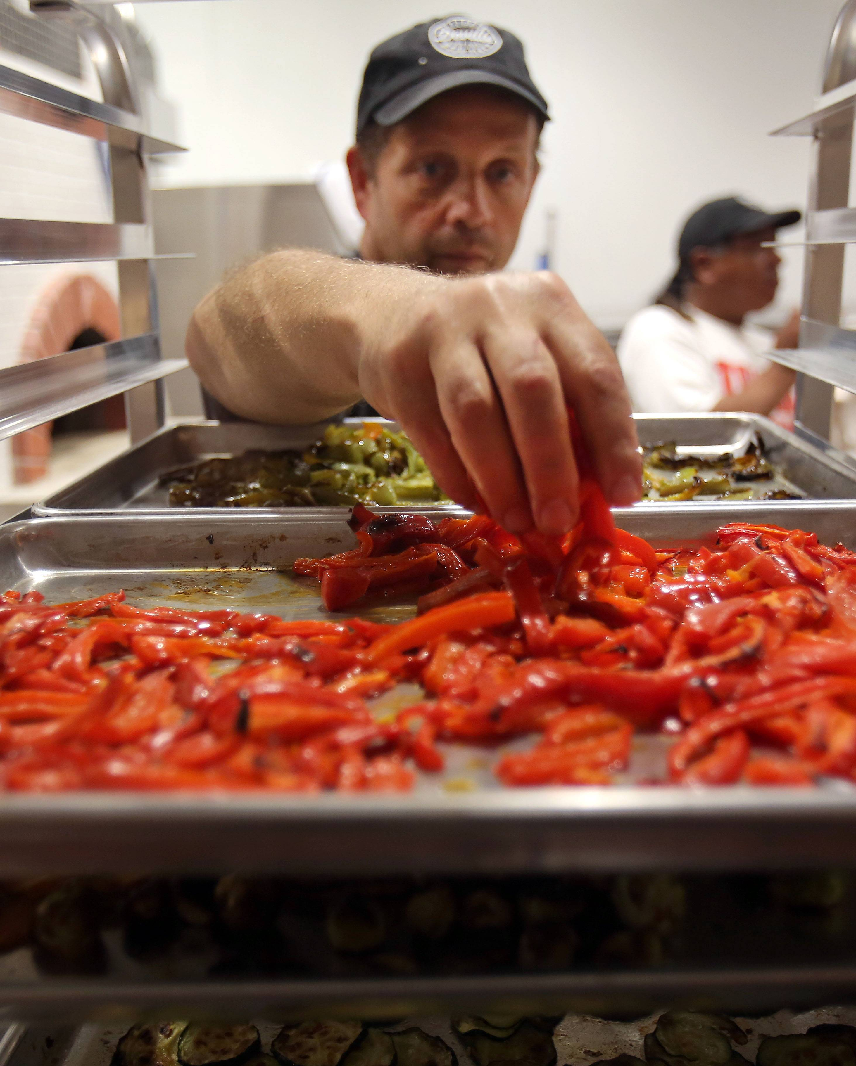 John Durning takes some roasted red peppers to make a pizza at his new Pizzeria DeVille in Libertyville.