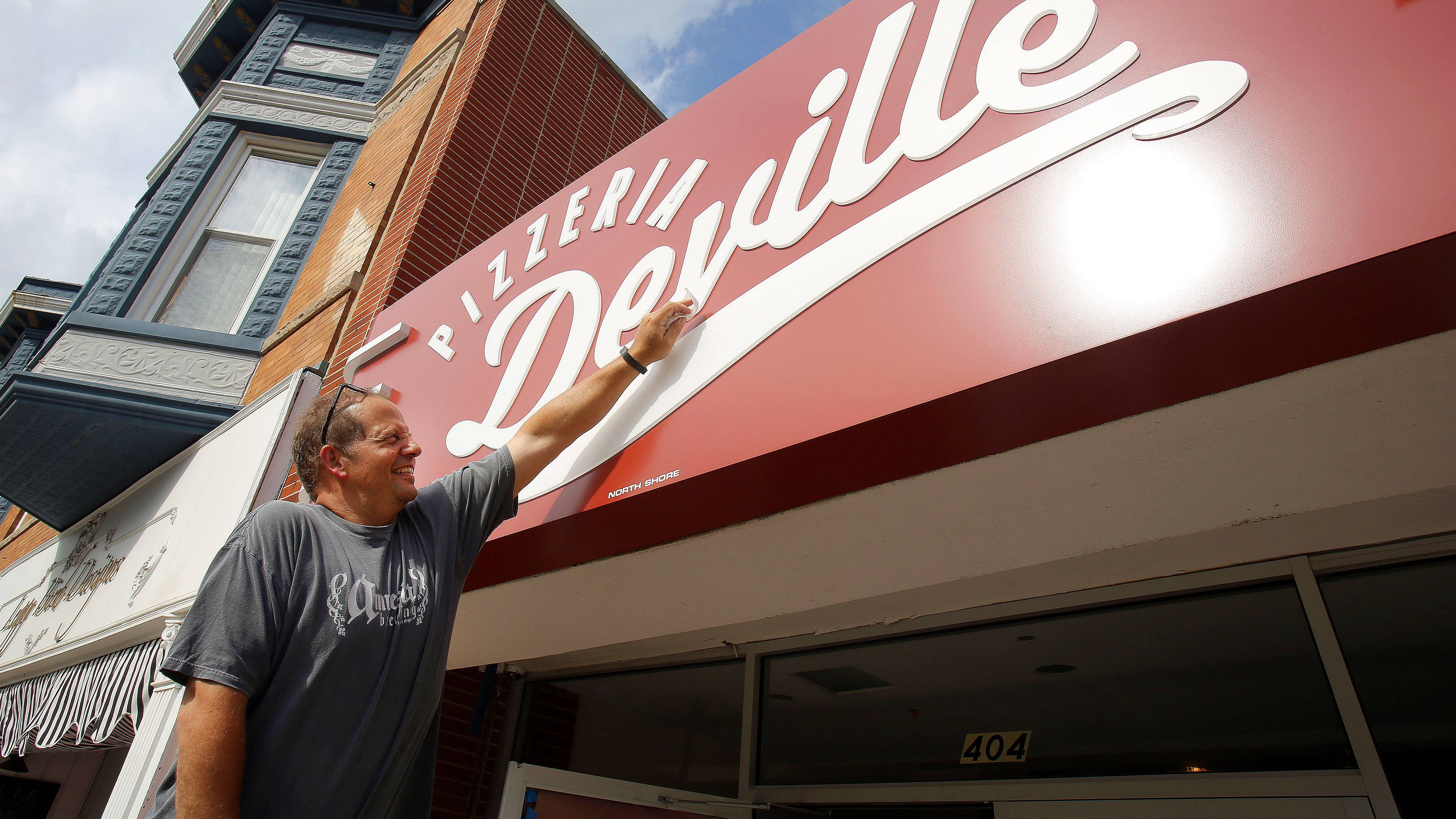 Proud pizzeria owner John During polishes the sign at his new Libertyville restaurant.
