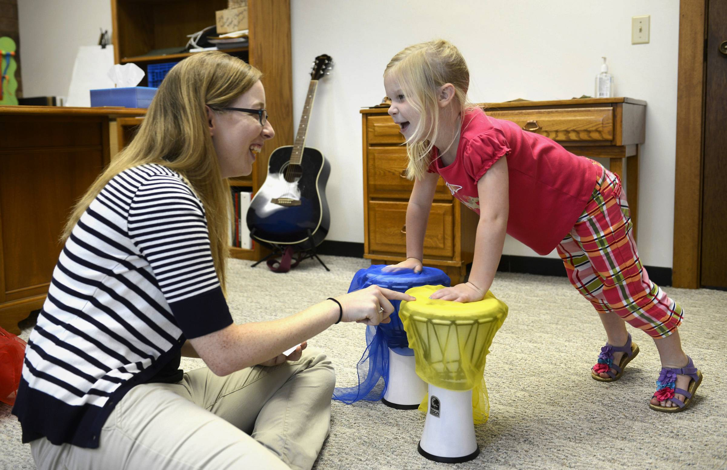 Music therapist Katie Fitch laughs with Ava Taylor, 5, during a session using drums to challenge Taylor's information processing at First Christian Church of Peoria.