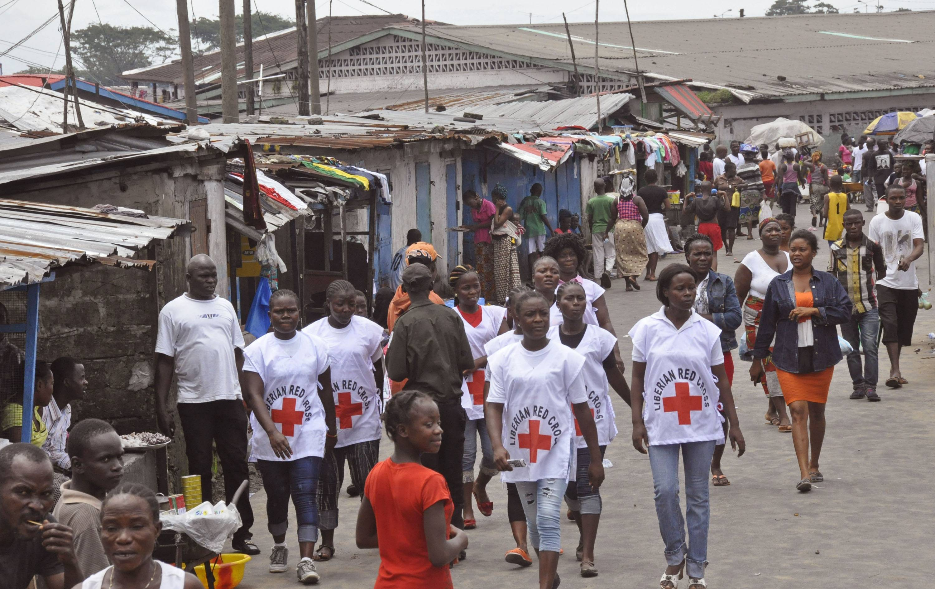 Red Cross workers walk through a section of West Point, an area that has been hit hard by the Ebola virus, with residents not allowed to leave as government forces clamp down on movement to prevent the spread of Ebola, in Monrovia, Liberia.
