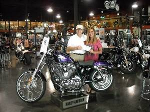 Roy Frank accepts a check from Deborah Joyce of the Illinois Harley-Davidson dealership in Countryside.