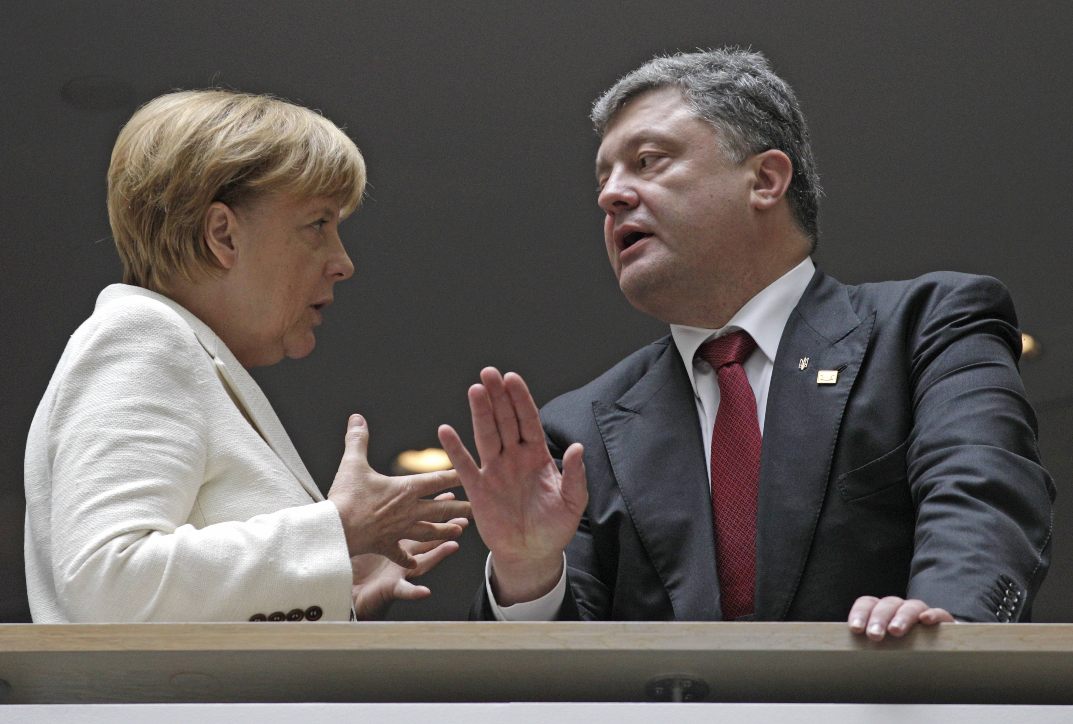 Ukrainian President Petro Poroshenko, right, talks with German Chancellor Angela Merkel during an European People's Party summit ahead of the EU summit in Brussels, Saturday.