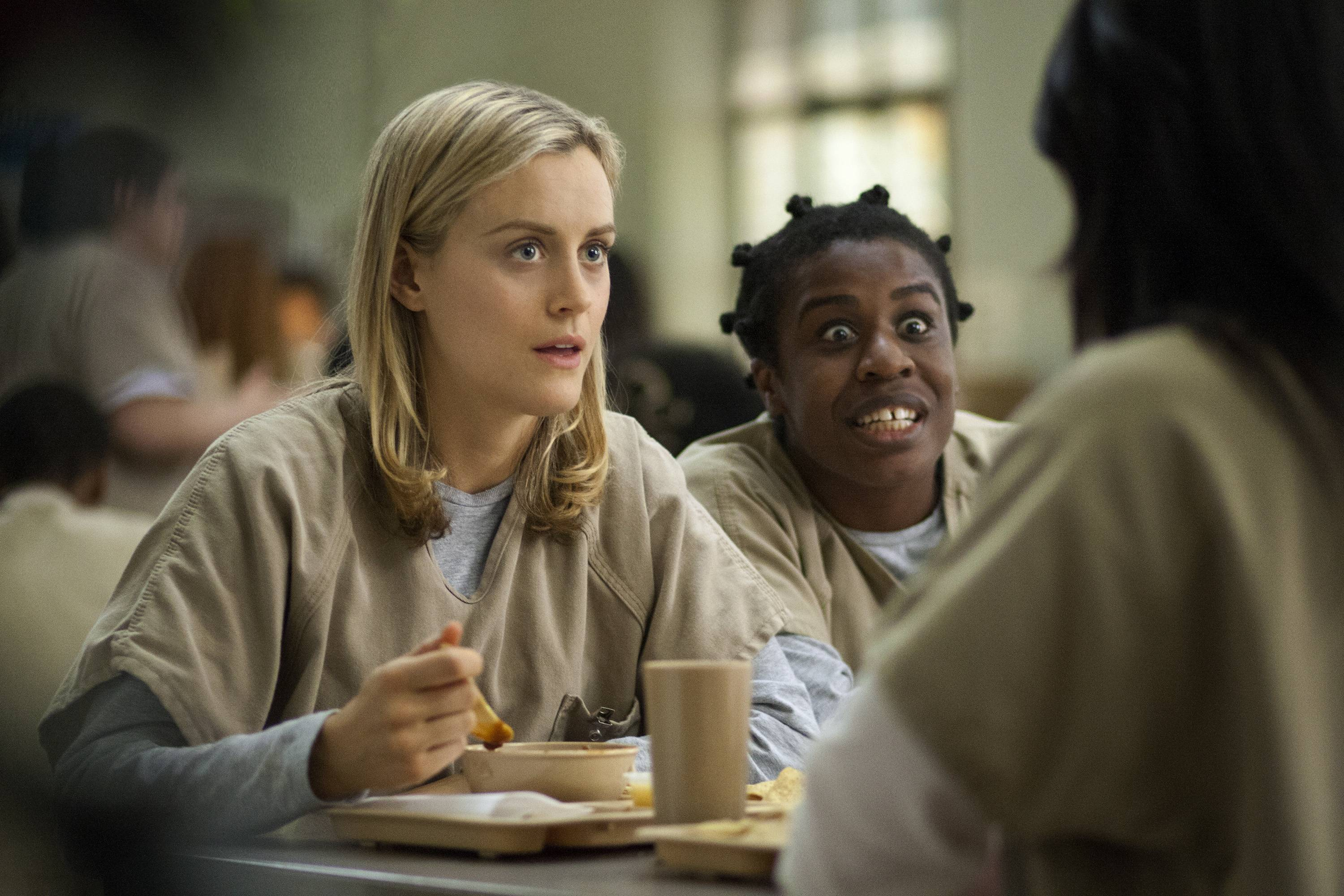 "This image released by Netflix shows Taylor Schilling, left, and Uzo Aduba in a scene from ""Orange Is the New Black."" Americans are increasingly engaging in a practice known as television binge-watching _ going through several episodes in a single stretch, rather than one a week, as was common before the advent of digital video recorders and Internet streaming services such as Netflix and Hulu."