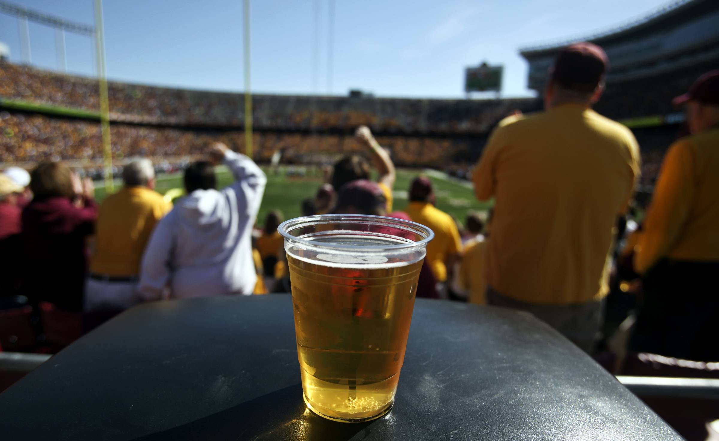 A beer sits atop a garbage can as Minnesota fans cheer a first quarter play against New Hampshire at TCF Bank Stadium in Minneapolis, Minn. A growing number of schools are capitalizing on fans' taste for the suds by bringing the party inside, opening taps in concourses that traditionally have been alcohol-free zones.