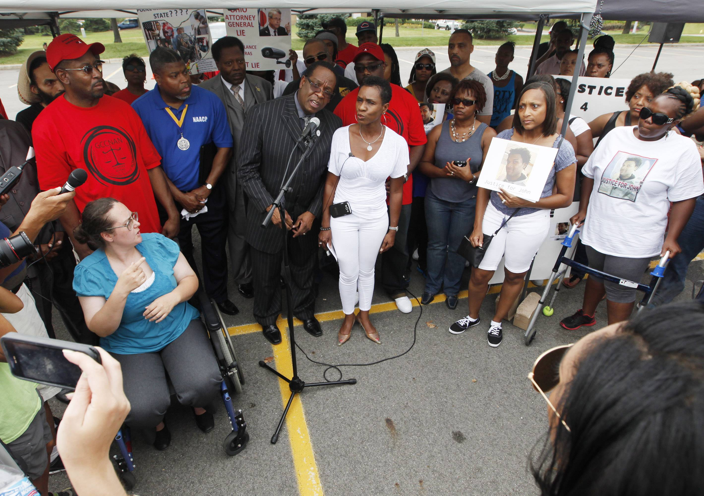 Bishop Bobby Hilton, center left at microphone, and Sharon Sherrod-Brown, aunt of John Crawford III, center right, take questions Saturday after a rally for Crawford in front of a Wal-Mart store in Beavercreek, Ohio.