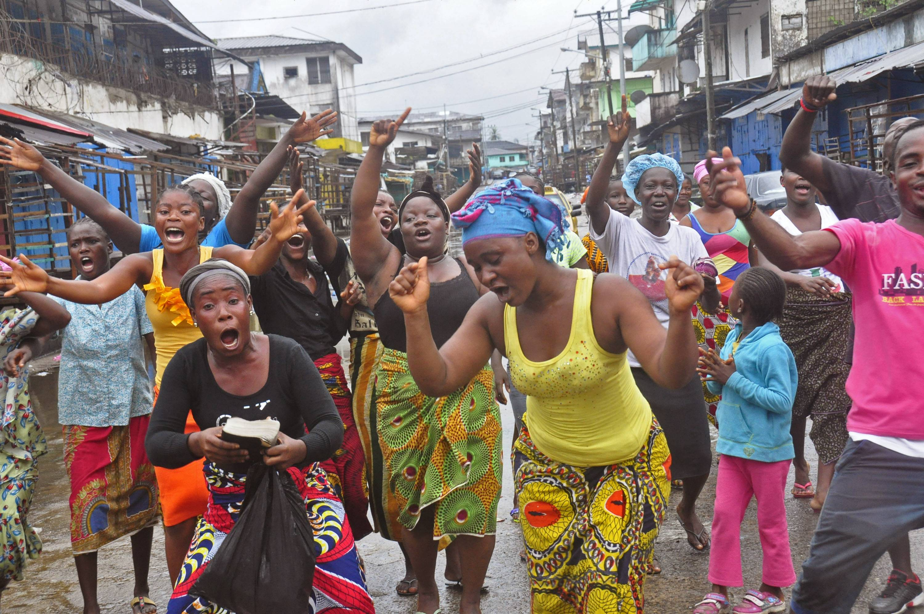 People celebrate in a street outside of West Point slum in Monrovia, Liberia, Saturday, Aug. 30. Crowds cheer and celebrate in the streets after Liberian authorities reopened a slum where tens of thousands of people were barricaded amid the country's Ebola outbreak. The slum of 50,000 people in Liberia's capital was sealed off more than a week ago, sparking unrest and leaving many without access to food or safe water.
