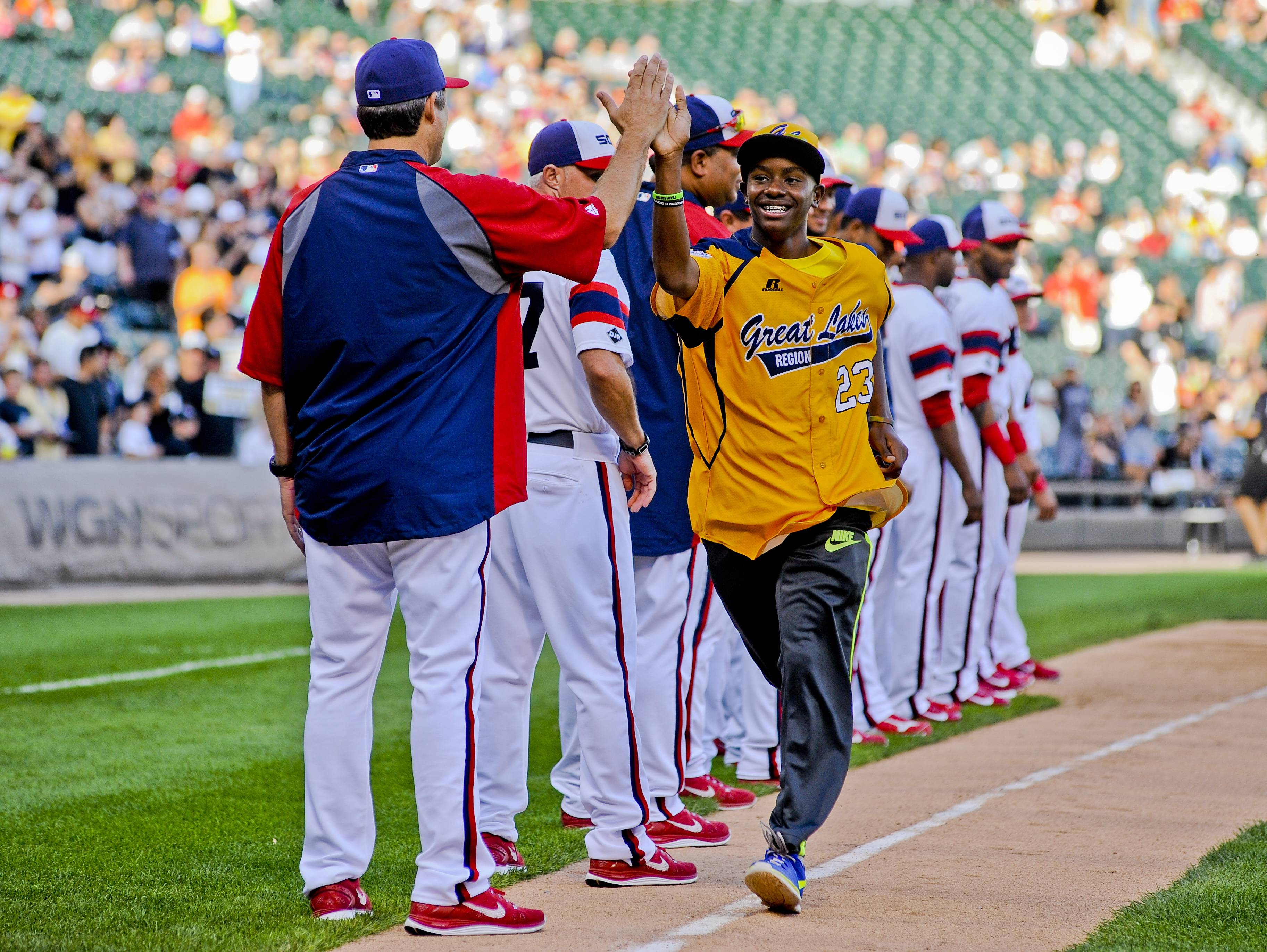 A member of the Jackie Robinson West Little League team high-fives a member of the White Sox as they were honored before the second game of the Sox's doubleheader against the Detroit Tigers Saturday at U.S. Cellular Field.