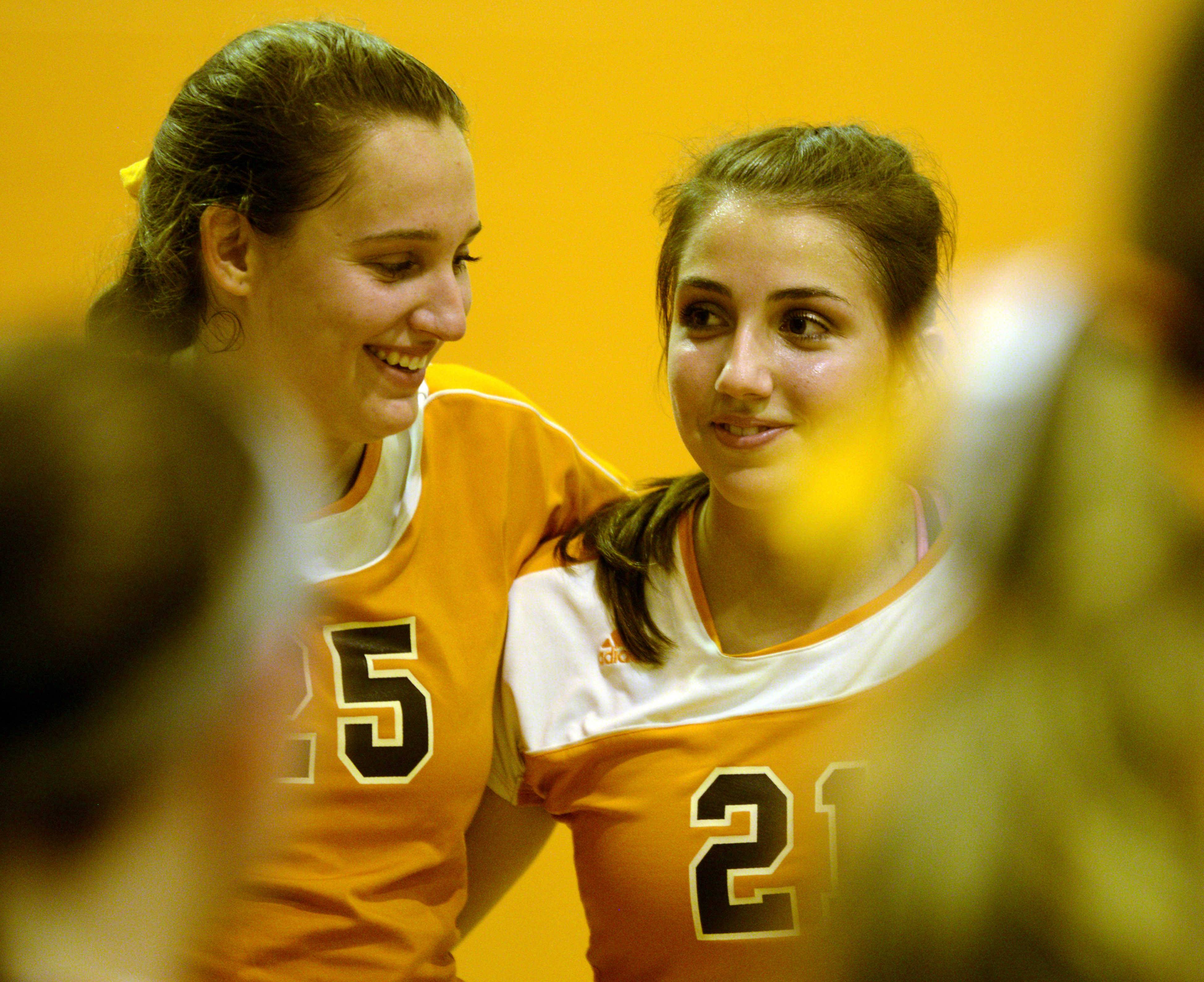 Hersey volleyball players Gabrielle Olhava, left, and Courtney Stedman, right, gather for a pregame cheer before Monday's game against Libertyville in the Ken Carter Gymnasium.