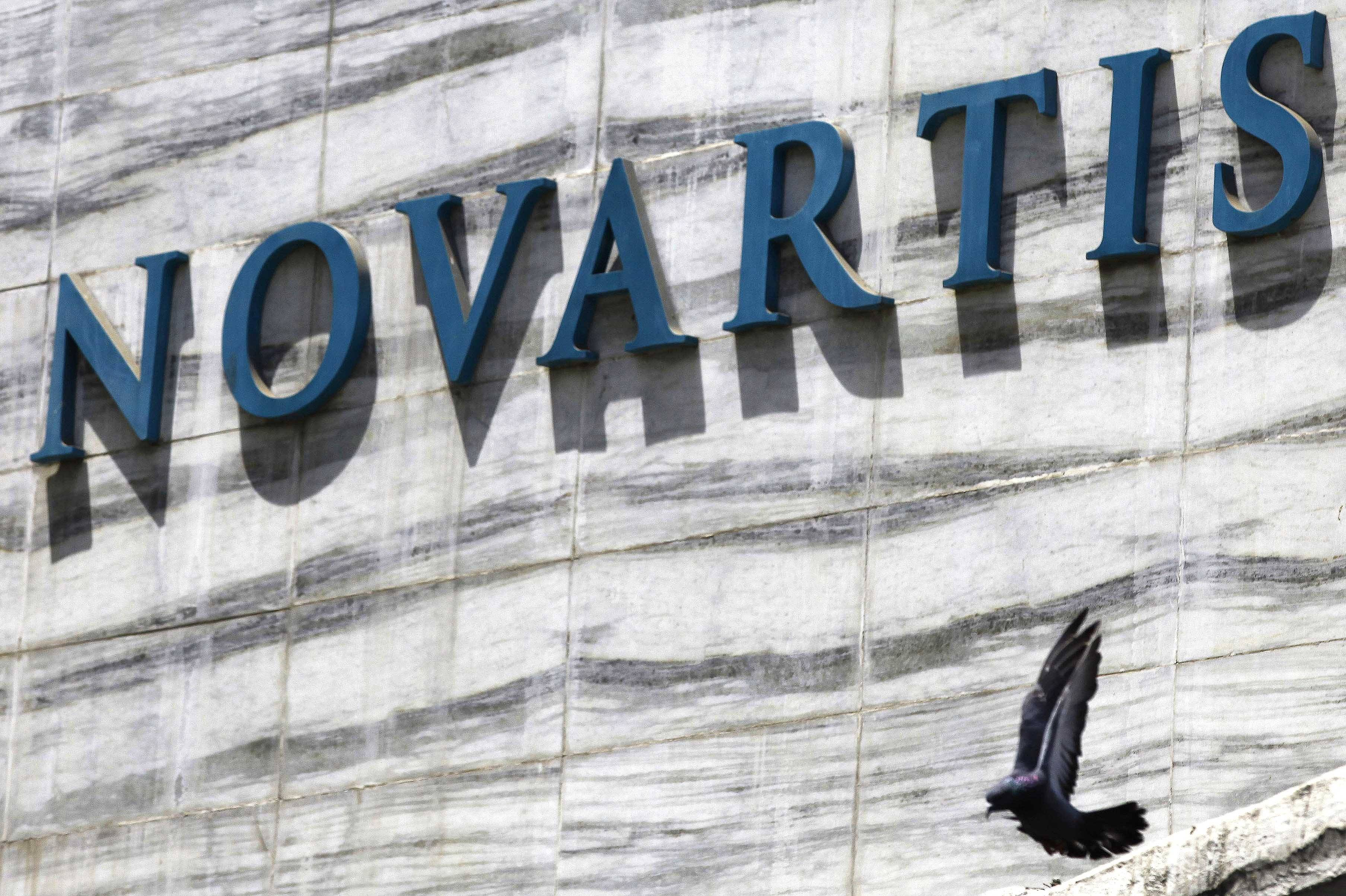 Associated Press/2013 A dove flies near the logo of Novartis India Limited at their head office in Mumbai, India.