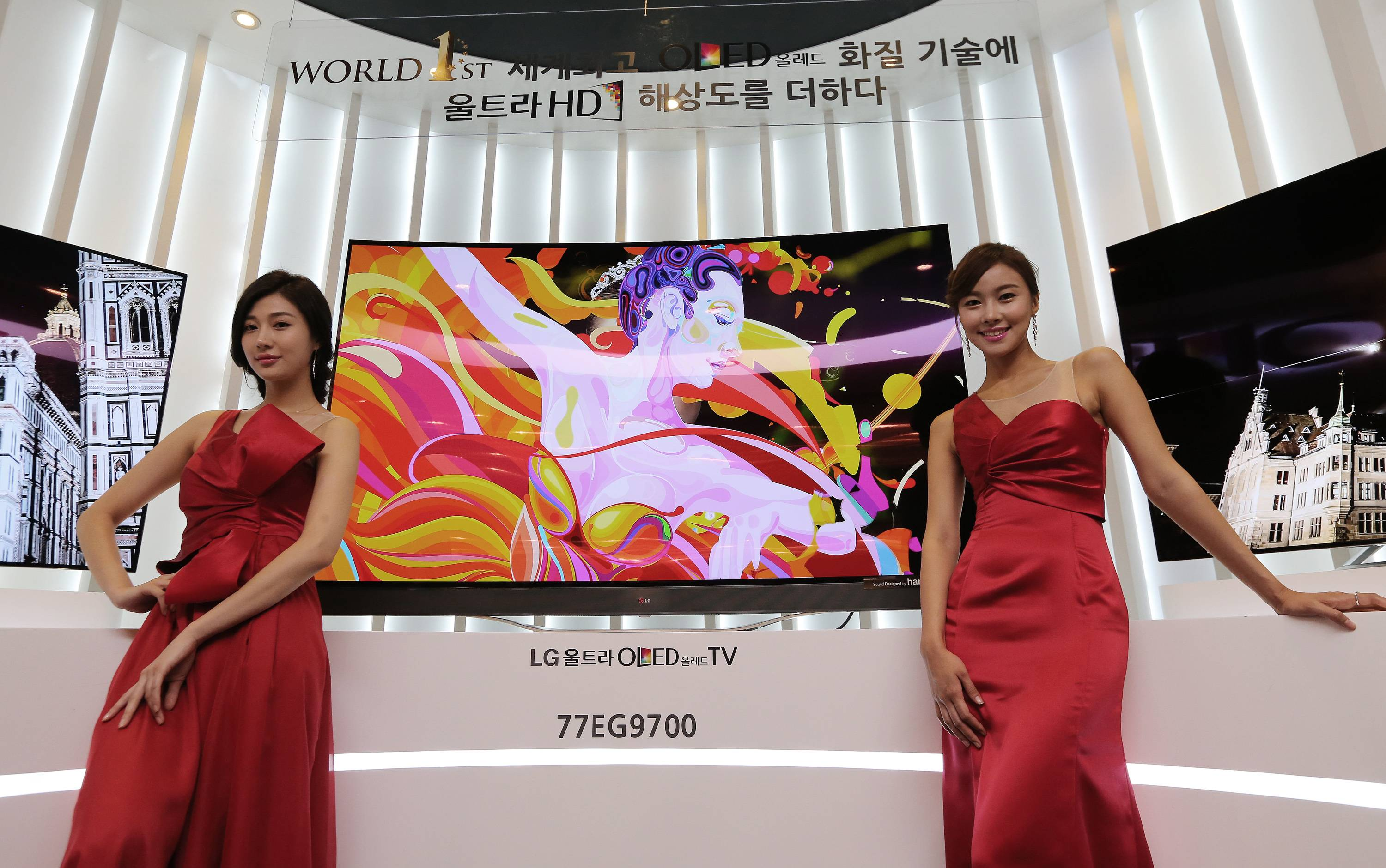 Models pose with LG Electronics' 77-inch Ultra organic light-emitting diode (OLED) TV Monday during a press unveiling in Seoul, South Korea. LG Electronics Inc. is sticking with its strategy of using the exceptionally expensive OLED display technology for TVs, announcing two new giant models with ultrahigh definition screens.