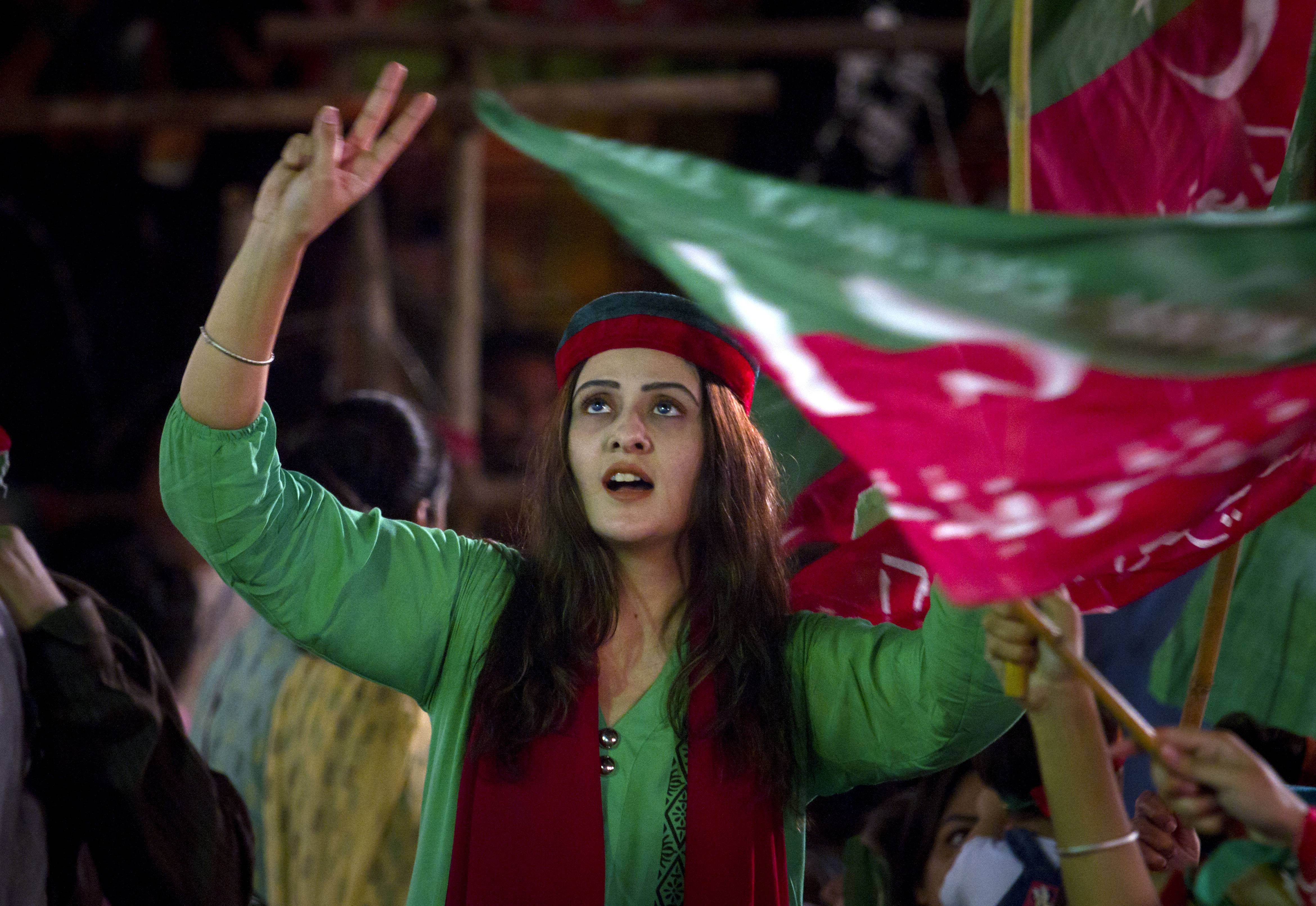 A woman supporter of Pakistan's cricketer-turned-politician Imran Khan flashes victory signs Saturday during a protest near the parliament building in Islamabad, Pakistan.