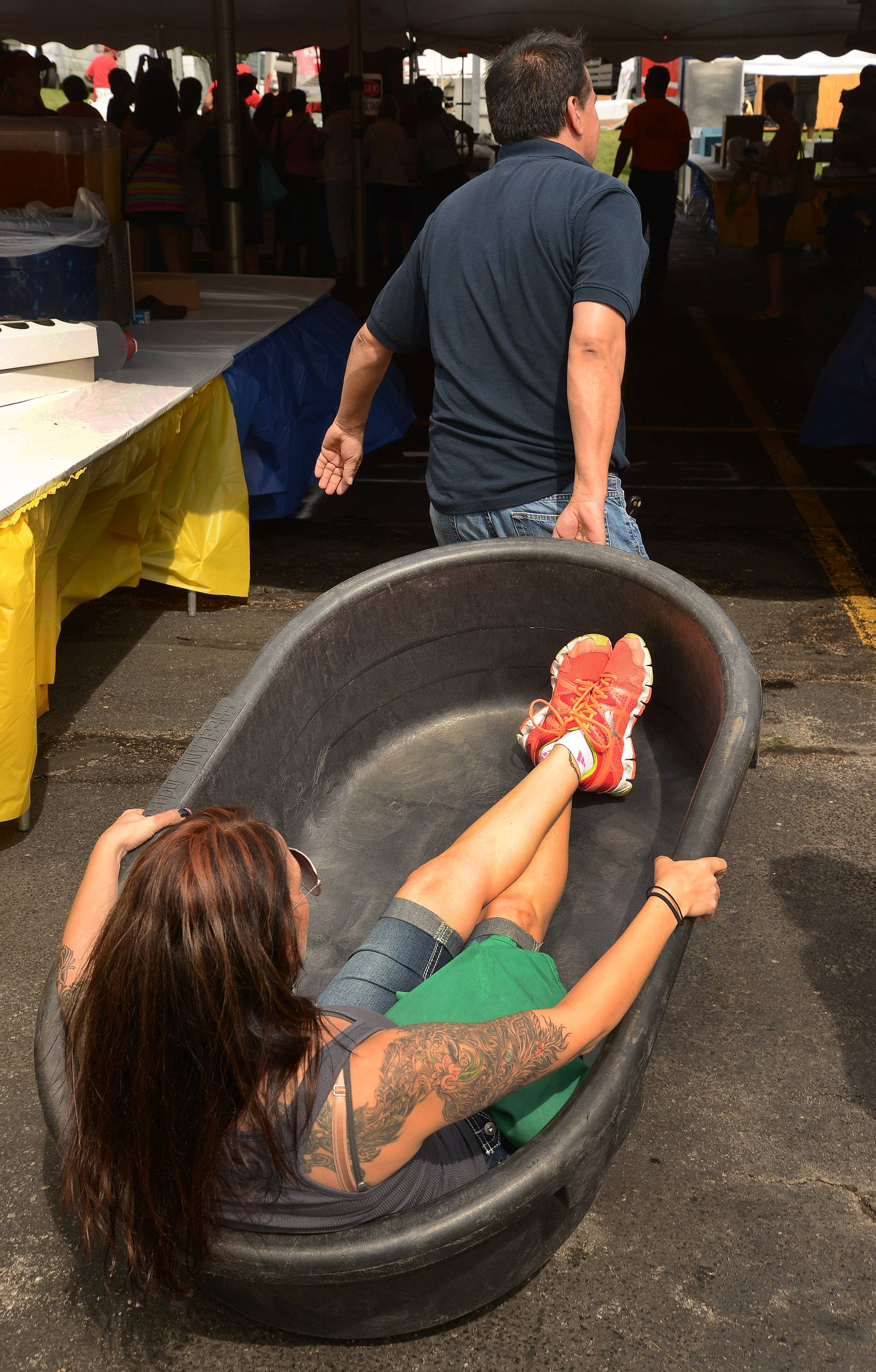 Jose Rodriguez hauls away Nikki Czapiga as she relaxes in the beer and ice tub while setting up for Village Tavern and Grill on the first day of Schaumburg's 44th annual Septemberfest.