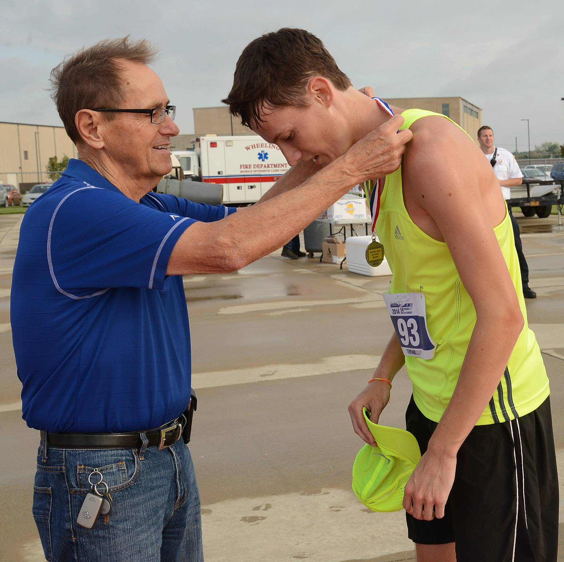 Prospect Heights Mayor Nick Helmer places a medal around the neck of Ryan Kearns of Prospect Heights for the fastest time of 17:28 in the inaugural Run the Runway 5K Run and 1 Mile Walk at Chicago Executive Airport in Wheeling.