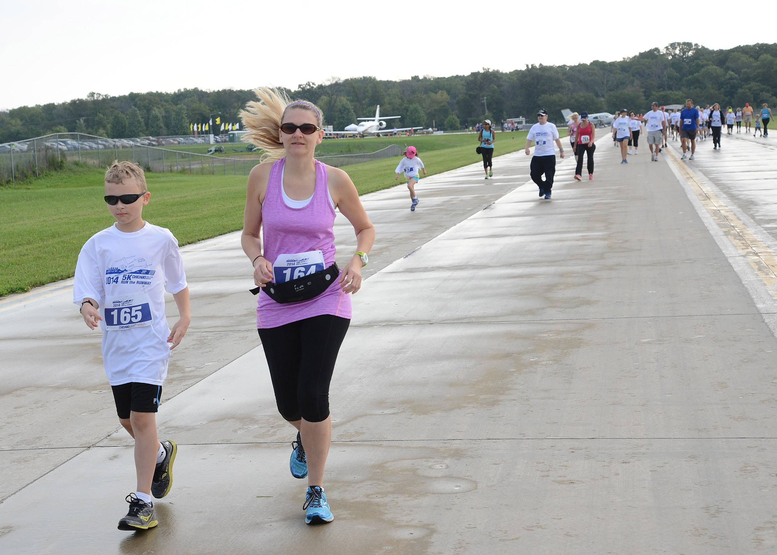 Sara and Nick Schroeder of Lake Zurich make their way down the runway during the Run the Runway 5K Run and 1 Mile Walk at Chicago Executive Airport in Wheeling.