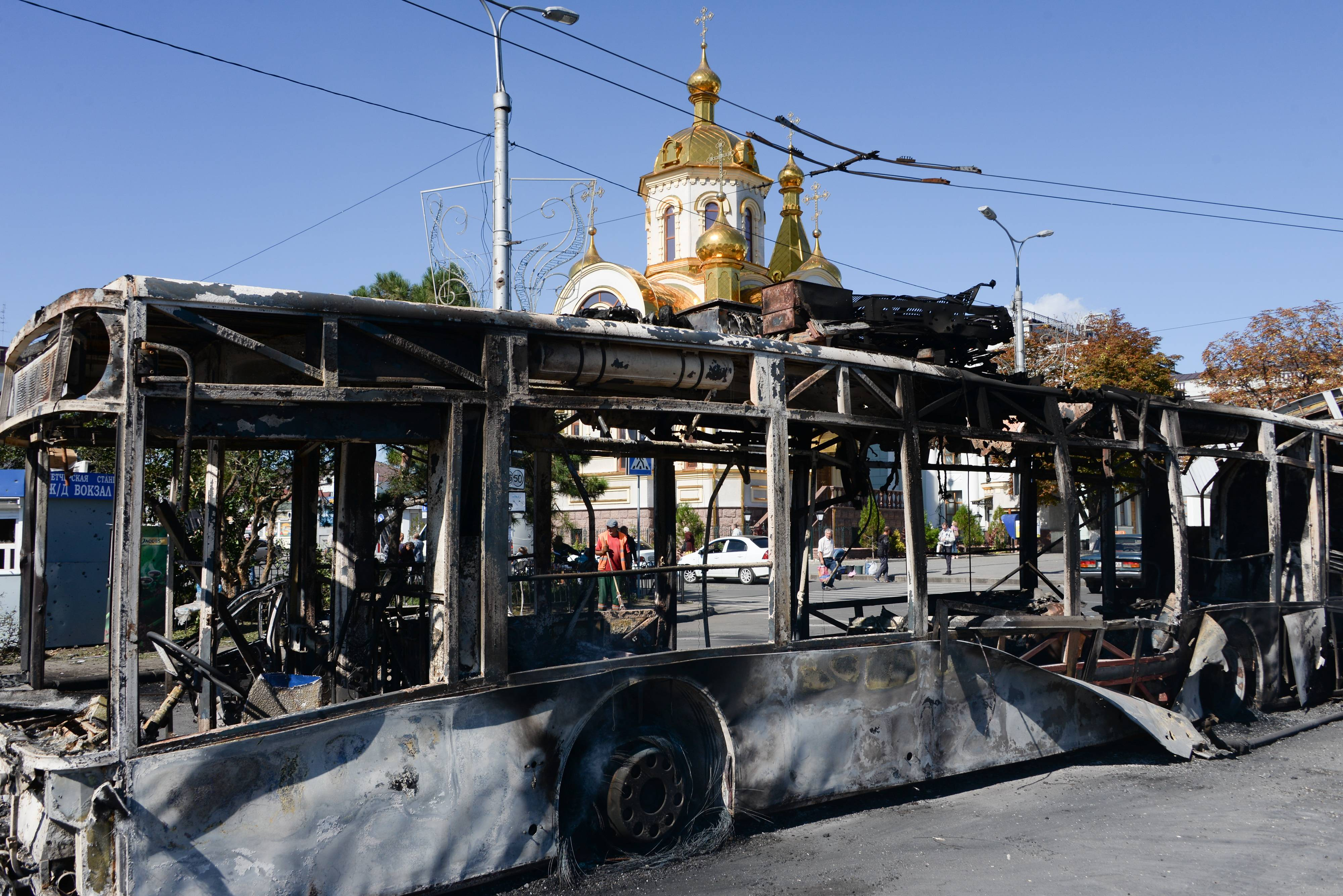 A burned trolley bus is seen near Donetsk train station after shelling, Donetsk, Ukraine, Saturday, Aug. 30. Heavy shelling from an unknown source hit a railway station and a nearby market on Friday evening in Donetsk, the largest rebel-held city in eastern Ukraine, an OSCE observer said at the site.