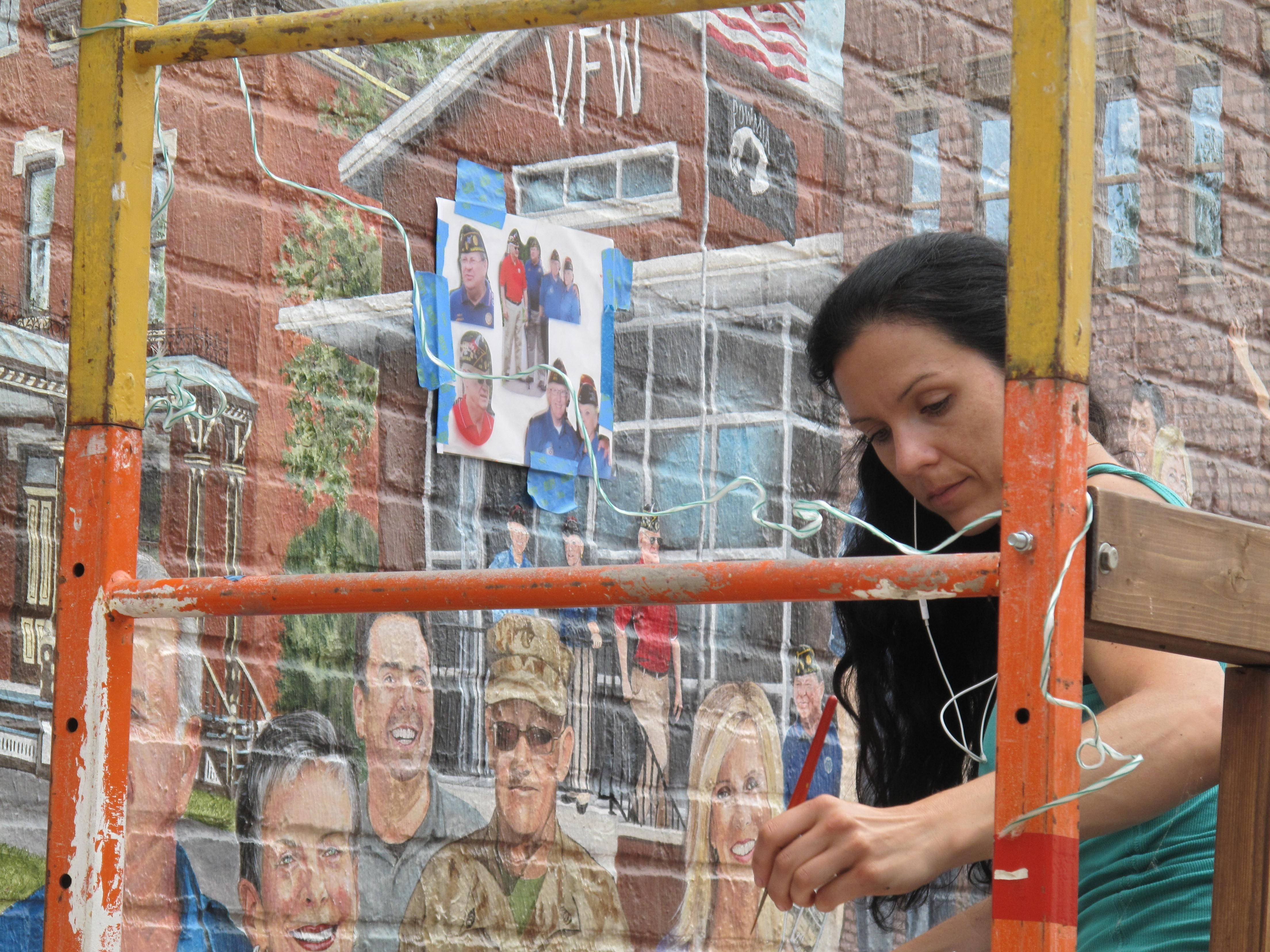 "Artist Adela Vystejnova works on the image of Judd Kendall VFW Post 3873 as part of the ""Naperville Loves a Parade"" mural, which will be dedicated at noon Monday in the ""Rubin's Way"" alley west of Main Street between Gap and Talbots in downtown Naperville."