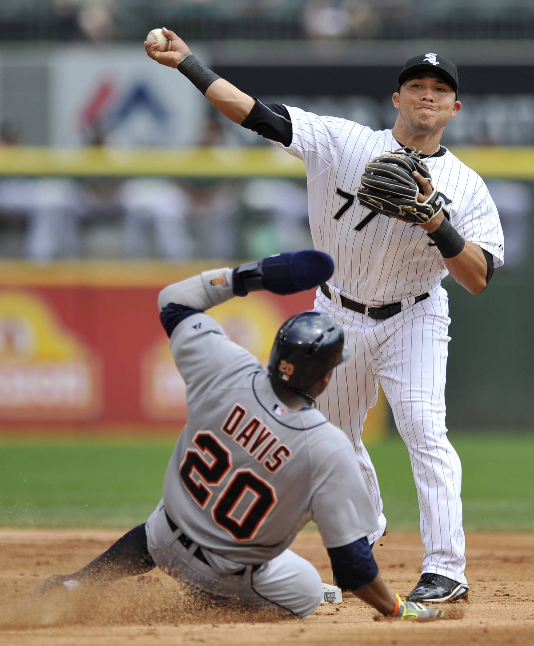 Chicago White Sox second baseman Carlos Sanchez (77), throws to first base after forcing out Detroit Tigers' Rajai Davis (20), at second base during the second inning of the first baseball game of a doubleheader  in Chicago, Saturday, Aug. 30, 2014.