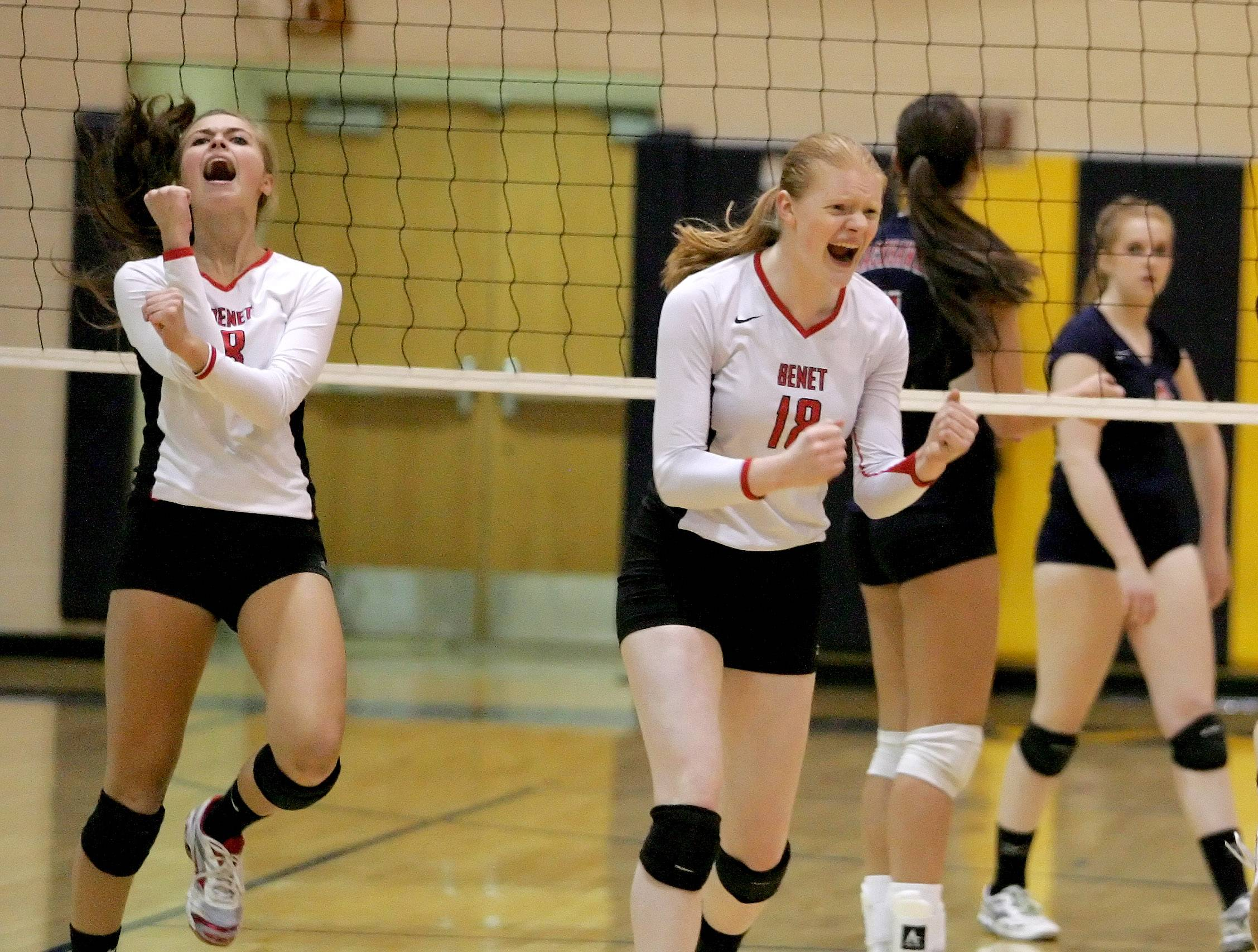 Nicki Barnes, left and Rachael Fara, right, of Benet, react to a point won during their 2-0 win over West Aurora in girls volleyball Neuqua Valley sectional semifinals in Naperville on Tuesday.
