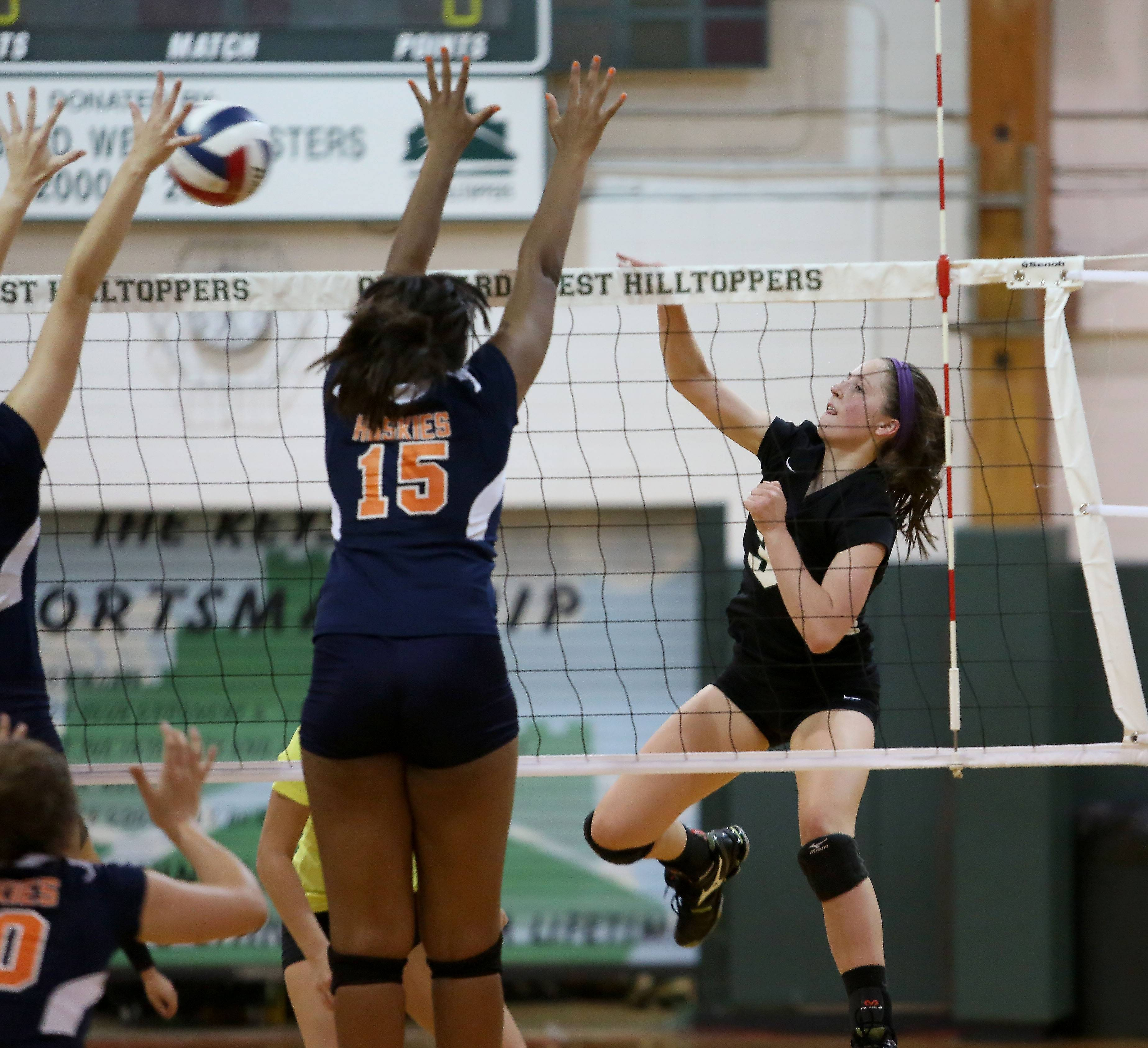 Alison Burelbach of Glenbard West spikes the ball against Oak Park River Forest during girls volleyball on Tuesday in Glen Ellyn.