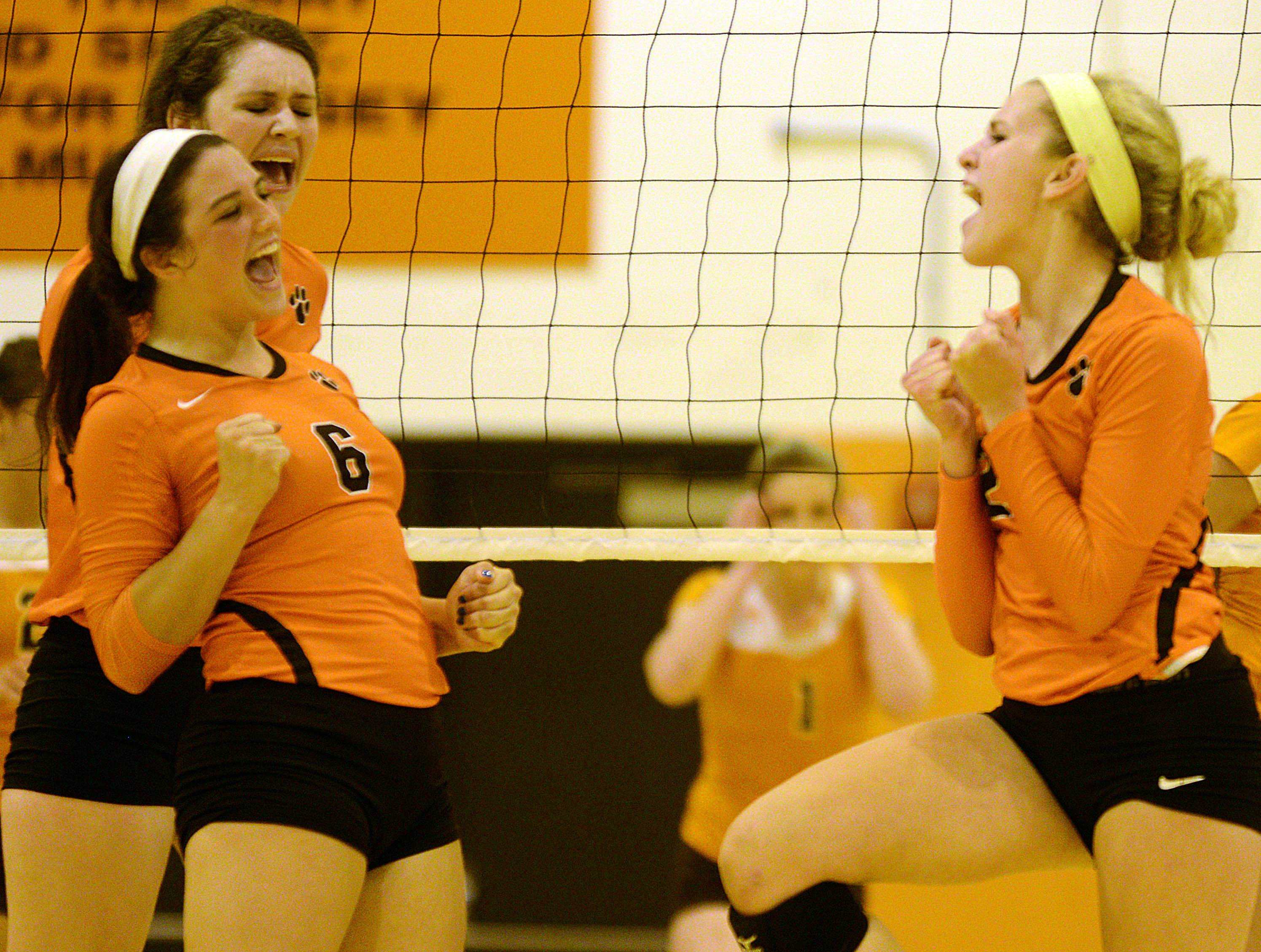 From left, Libertyville's Lizzie Apgar (6), Alex Basler and Sinead Prentiss celebrate a point during the Wildcats' victory at Hersey on Monday.