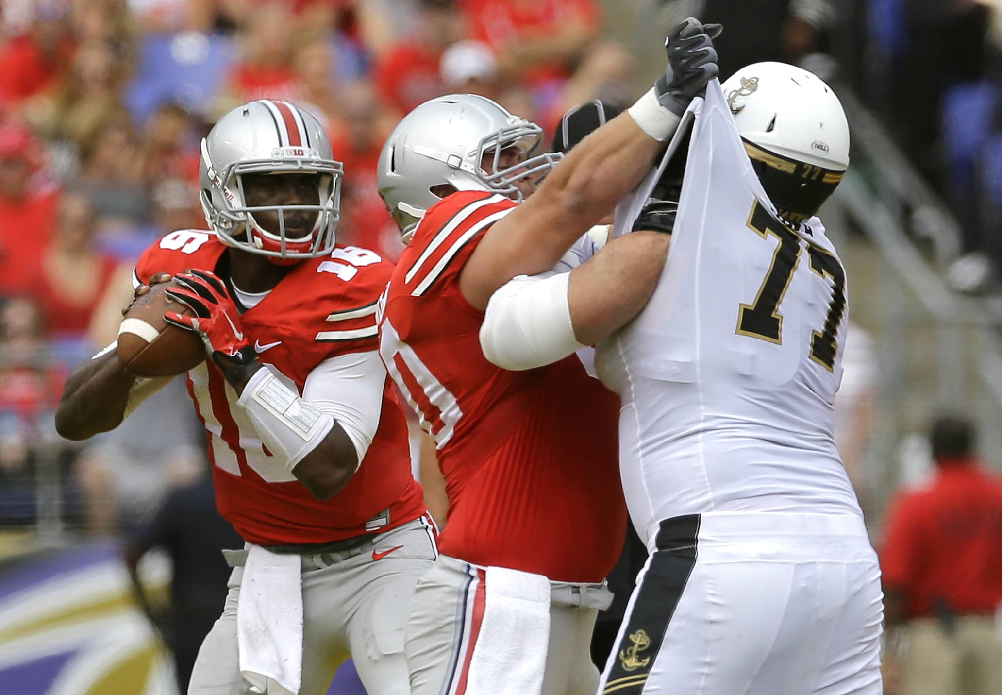 Ohio State quarterback J.T. Barrett, left, looks for a receiver as center Jacoby Boren blocks Navy guard Bernard Sarra during the first half Saturday in Baltimore.