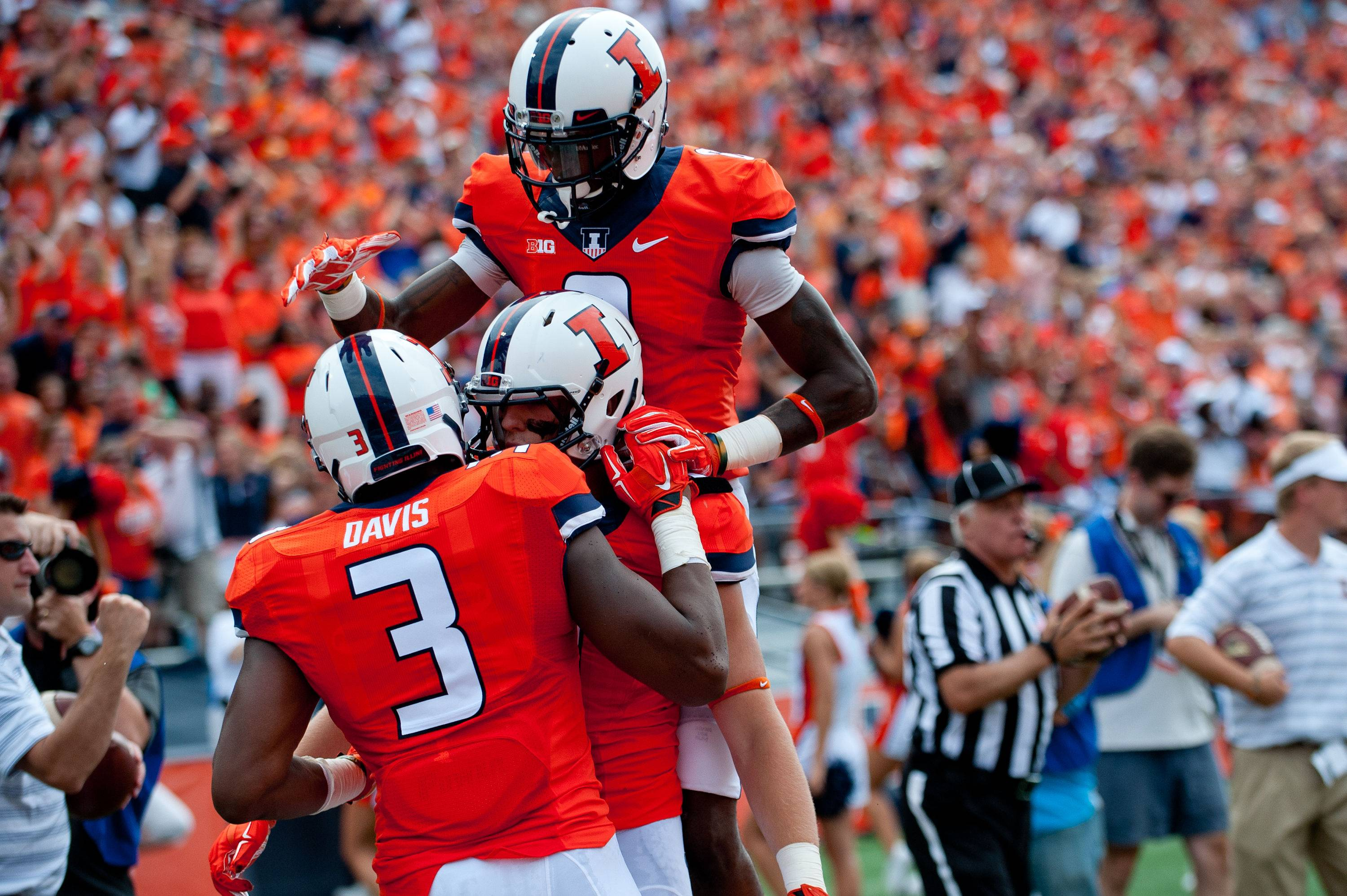 Illinois tight end Jon Davis (3) is congratulated by teammate Matt LaCosse (11) and  wide receiver Geronimo Allison (8), top, after scoring a touchdown Saturday during the second quarter of an NCAA college football game against Youngstown State at Memorial Stadium in Champaign.