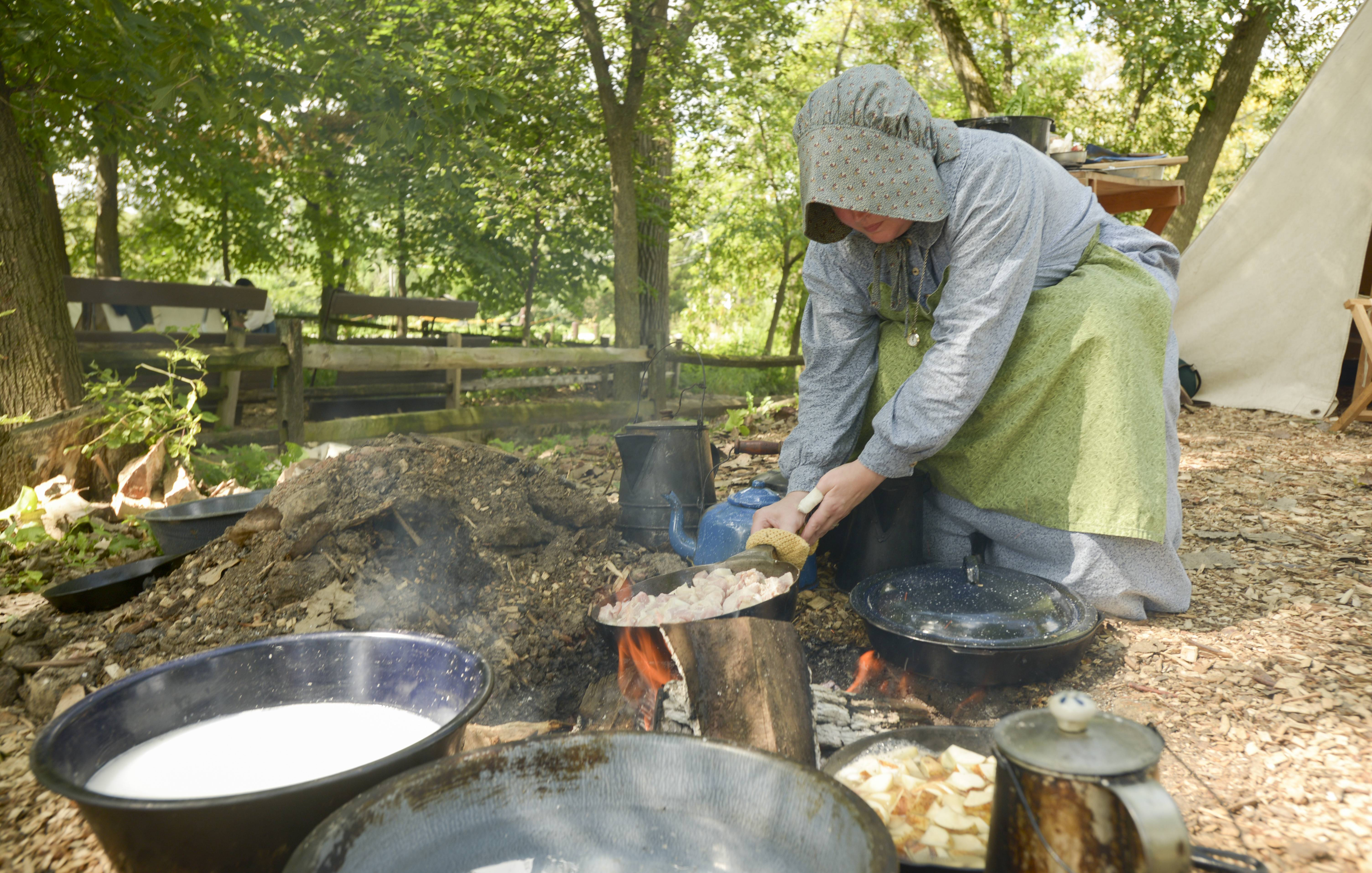 Luetta Coonrod of Lombard demonstrates how food was cooked at Union Army camps during the Civil War Encampment on Sunday at Graue Mill and Museum in Oak Brook. the event also featured combat and medical demonstrations from the Civil War era.