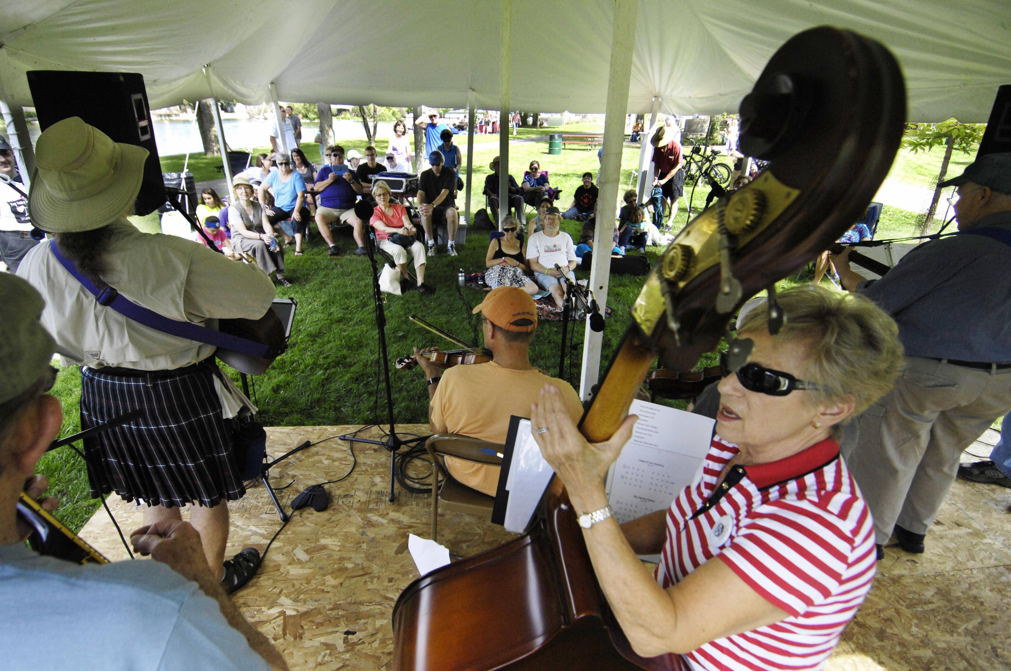 Members of The Plank Road Folk Song Society, including Jen Shilt on the Bass, perform for the crowd Sunday at the Fox Valley Folk Festival at Island Park in Geneva. The festival continues from 11 a.m. to 6 p.m. Monday.