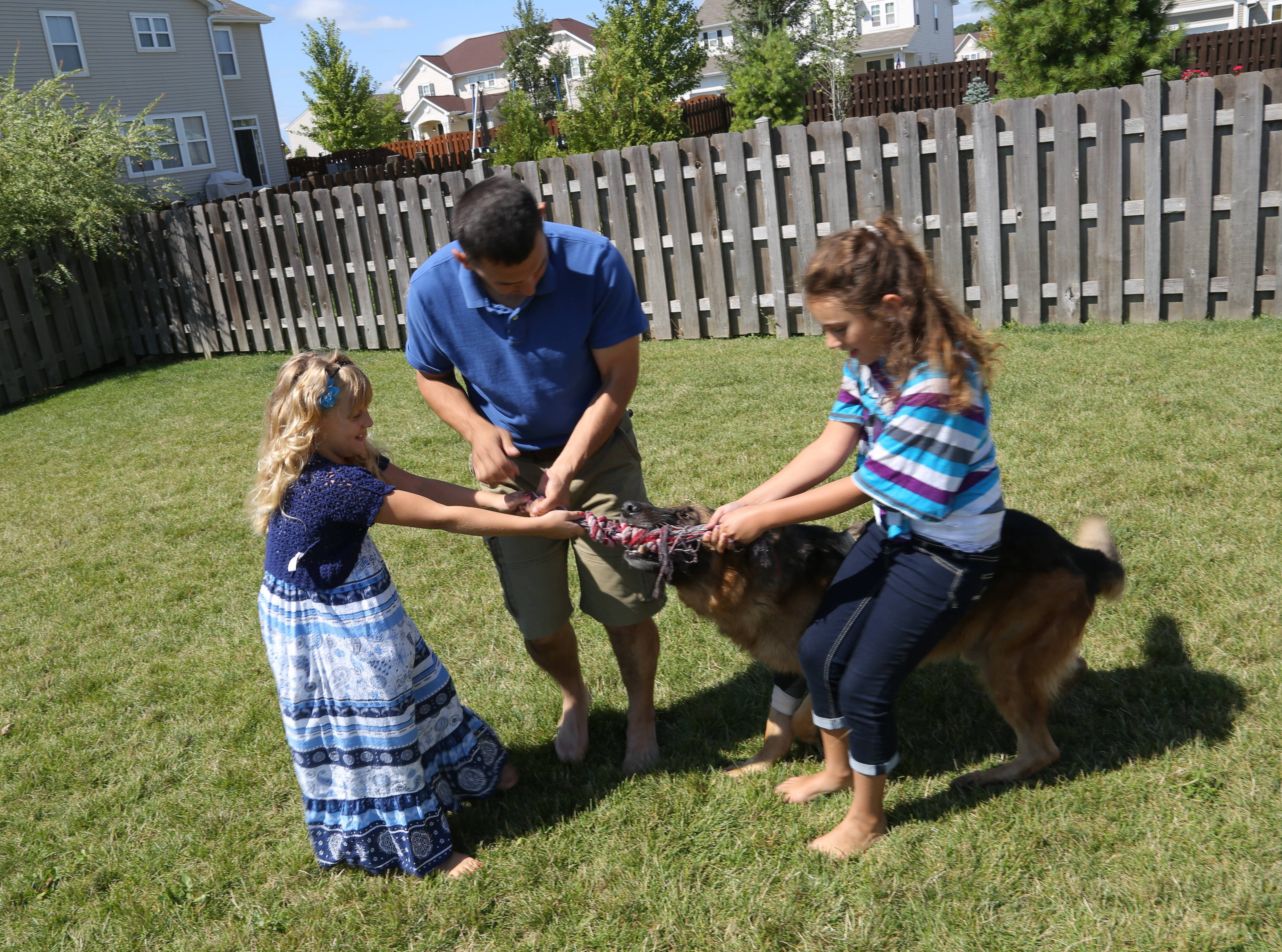 Gurnee Police Officer Phil Mazur and his daughters Kailey, 10, right, and Allison, 8, play in their backyard with retired police dog Shane, 9, at their home in Kenosha, Wisconsin.