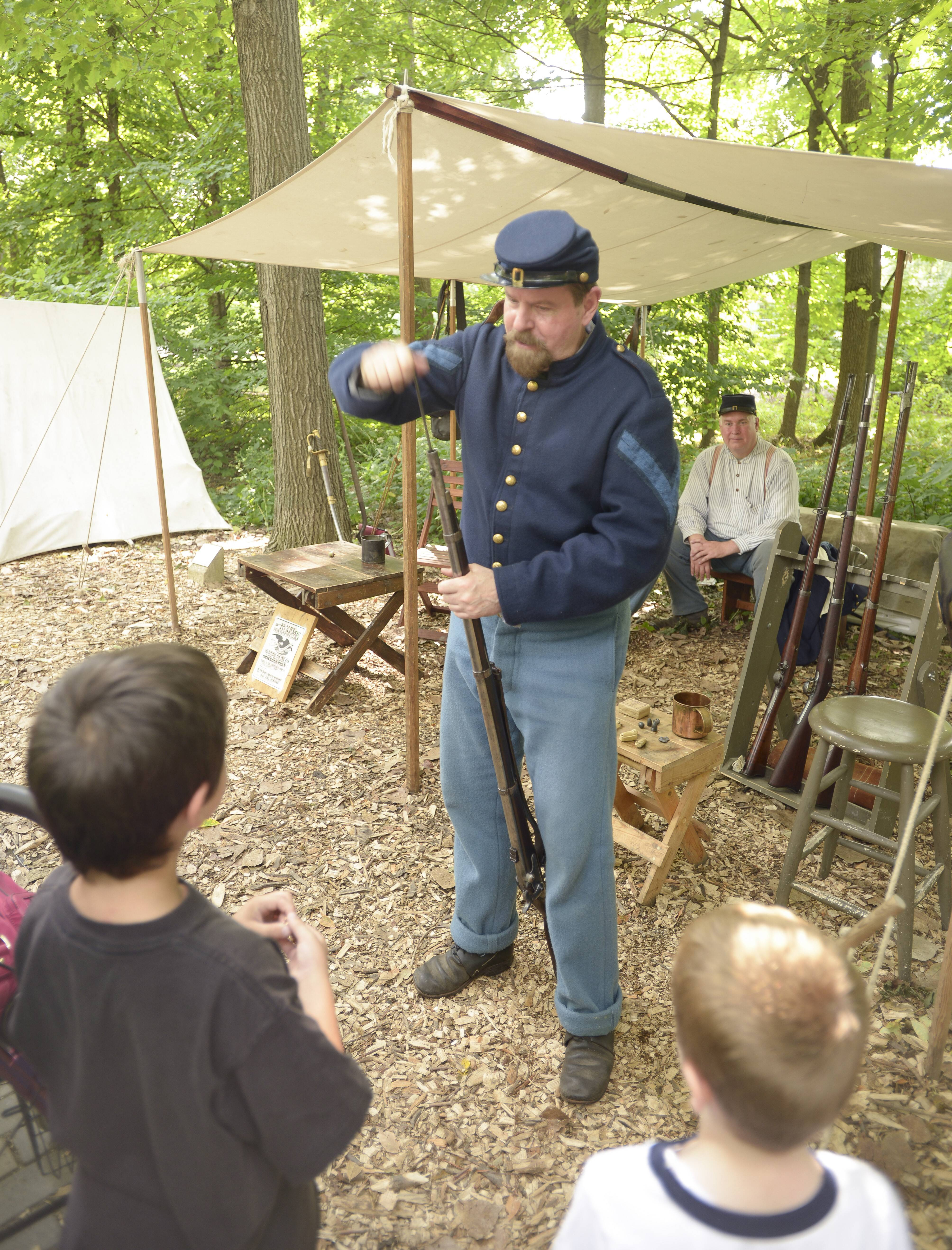 Bob Winter of Lombard, who has been involved in Civil War re-enacting for 25 years, shows how to load a rifle during the Civil War Encampment on Sunday at Graue Mill and Museum in Oak Brook.