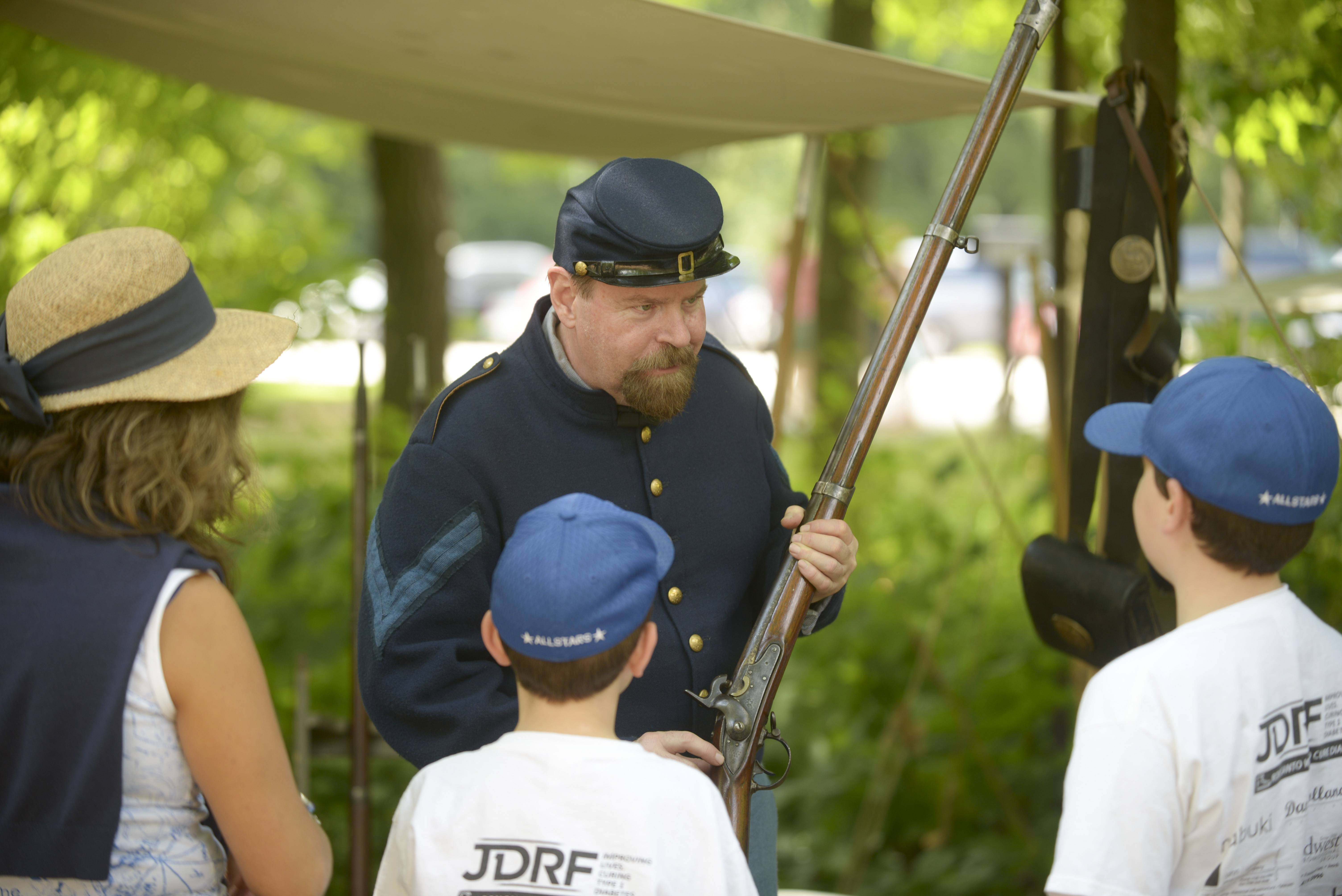 Bob Winter of Lombard, who has been involved in Civil War re-enacting for 25 years, talks to visitors Sunday at the Civil War Encampment at Graue Mill and Museum in Oak Brook. The event featured demonstrations of combat tactics and medical treatment from the Civil War era.