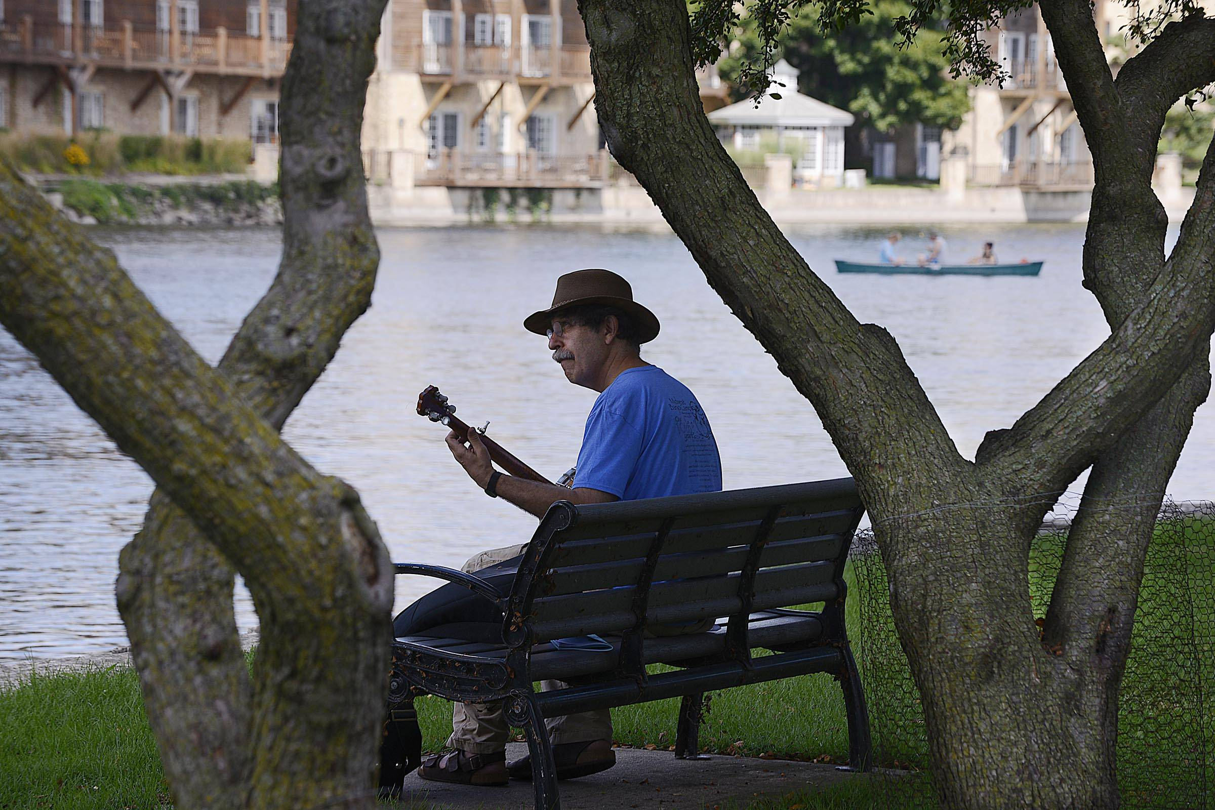 Ken Perlman, of Boston, plays his five-string banjo on the banks of the Fox River before perfuming for the crowd Sunday at the Fox Valley Folk Festival at Island Park in Geneva. The festival continues from 11 a.m. to 6 p.m. Monday.