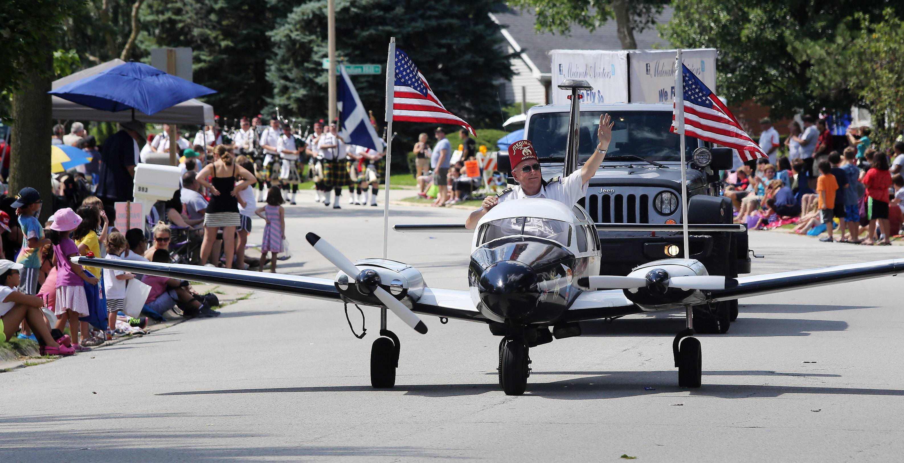 Gerry Olsen of the Medinah Shriner's Aviators rides in a plane Sunday during the Buffalo Grove Days parade Sunday along Bernard Drive. The organization transports children who are burn victims to burn unit hospitals.