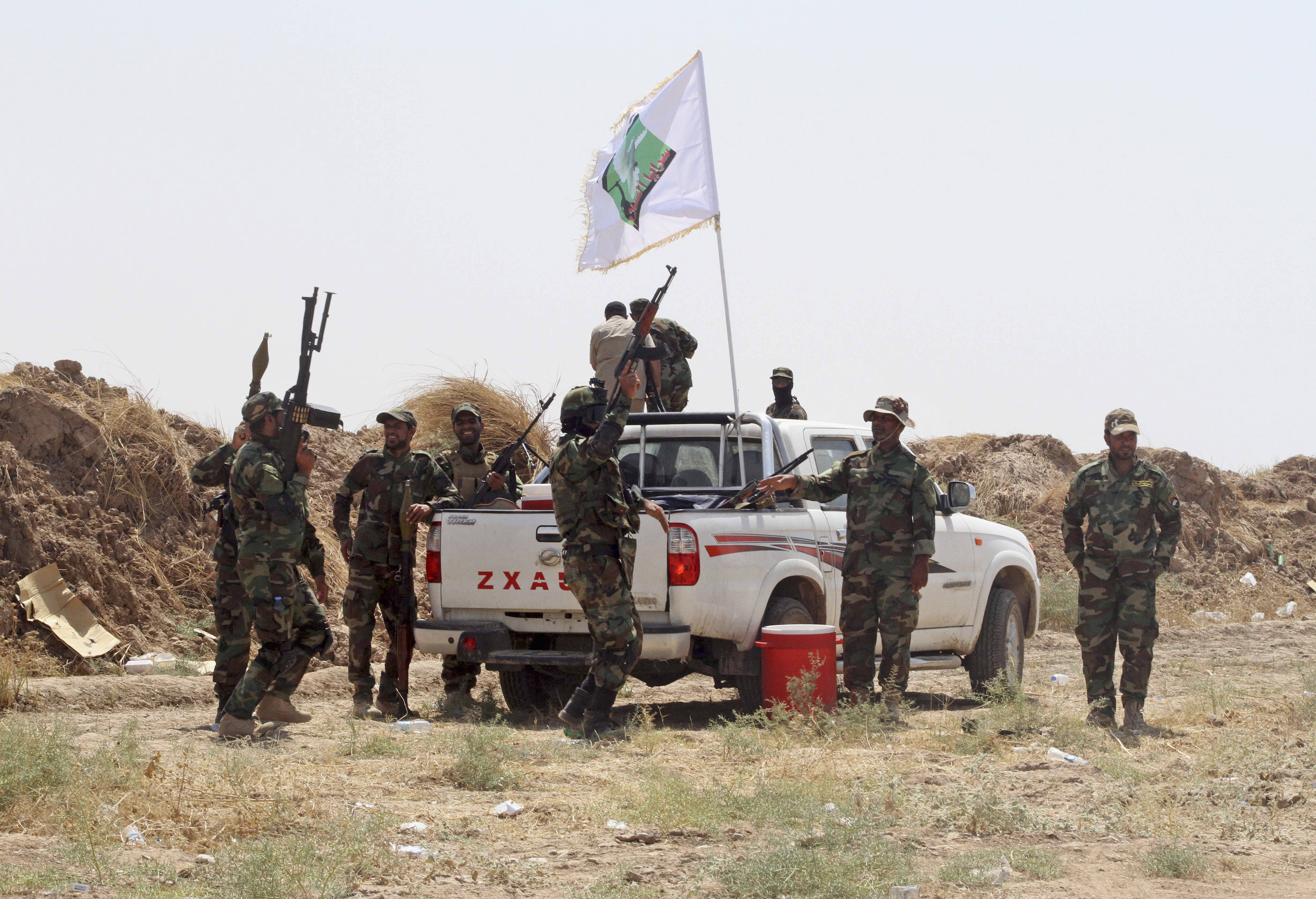 Iraqi security forces and Shiite militiamen celebrate after breaking the siege on 15,000 Shiite Turkmens stranded in the farming community town of Amirli, north of Baghdad, Sunday. The Islamic State extremist group has seized cities, towns and vast tracts of land in northeastern Syria and northern and western Iraq. It views Shiites as apostates and has carried out a number of massacres and beheadings -- often posting grisly videos and photos of the atrocities online.