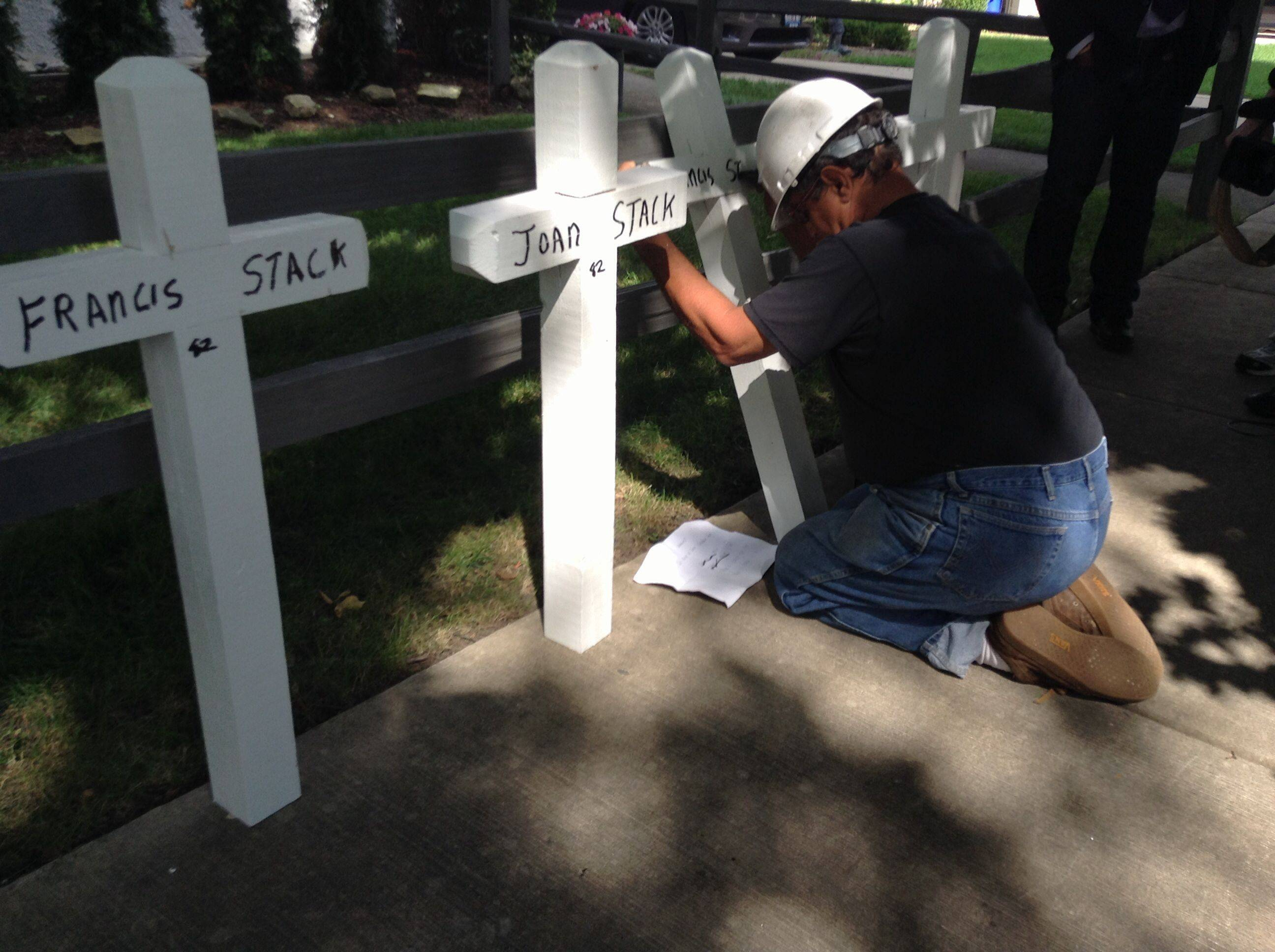 Greg Zanis, of Aurora, places white crosses with the names of the four members of Stack family outside the family's Elmhurst home Sunday morning. Francis, Joan, Mary and Francis Stack Jr. died in what police are calling a triple murder and suicide.