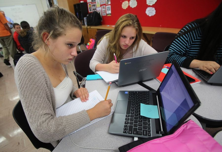 Mundelein High School freshmen Madison Guin, left, and Hailey Klebek work on Chromebooks in an algebra class. Every student received a Chromebook when the 2014-15 term began a few weeks ago.