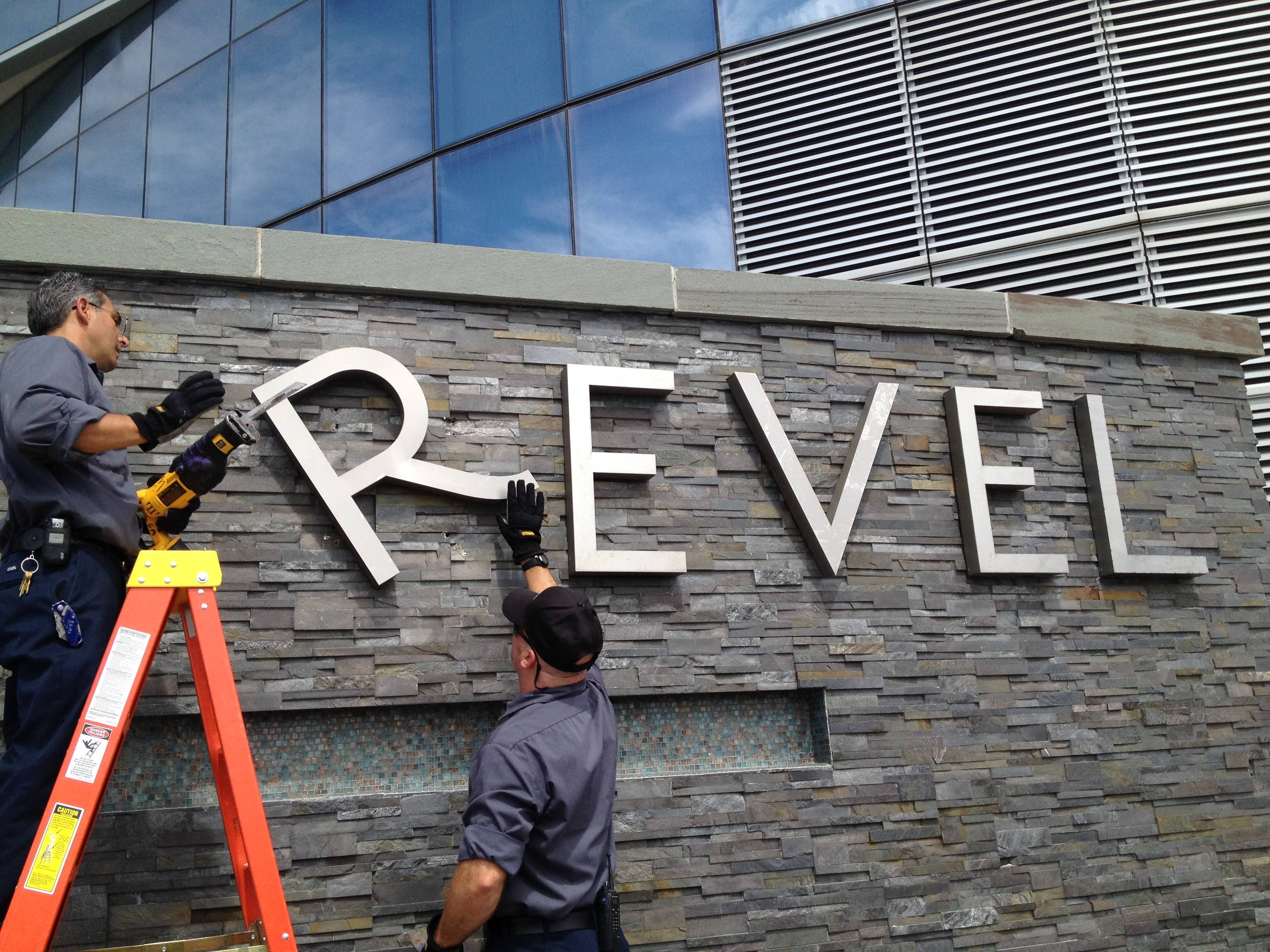Revel employees remove letters from a sign at the Revel hotel-casino Monday in Atlantic City, N.J. The hotel closed Monday and the casino will close on Tuesday.
