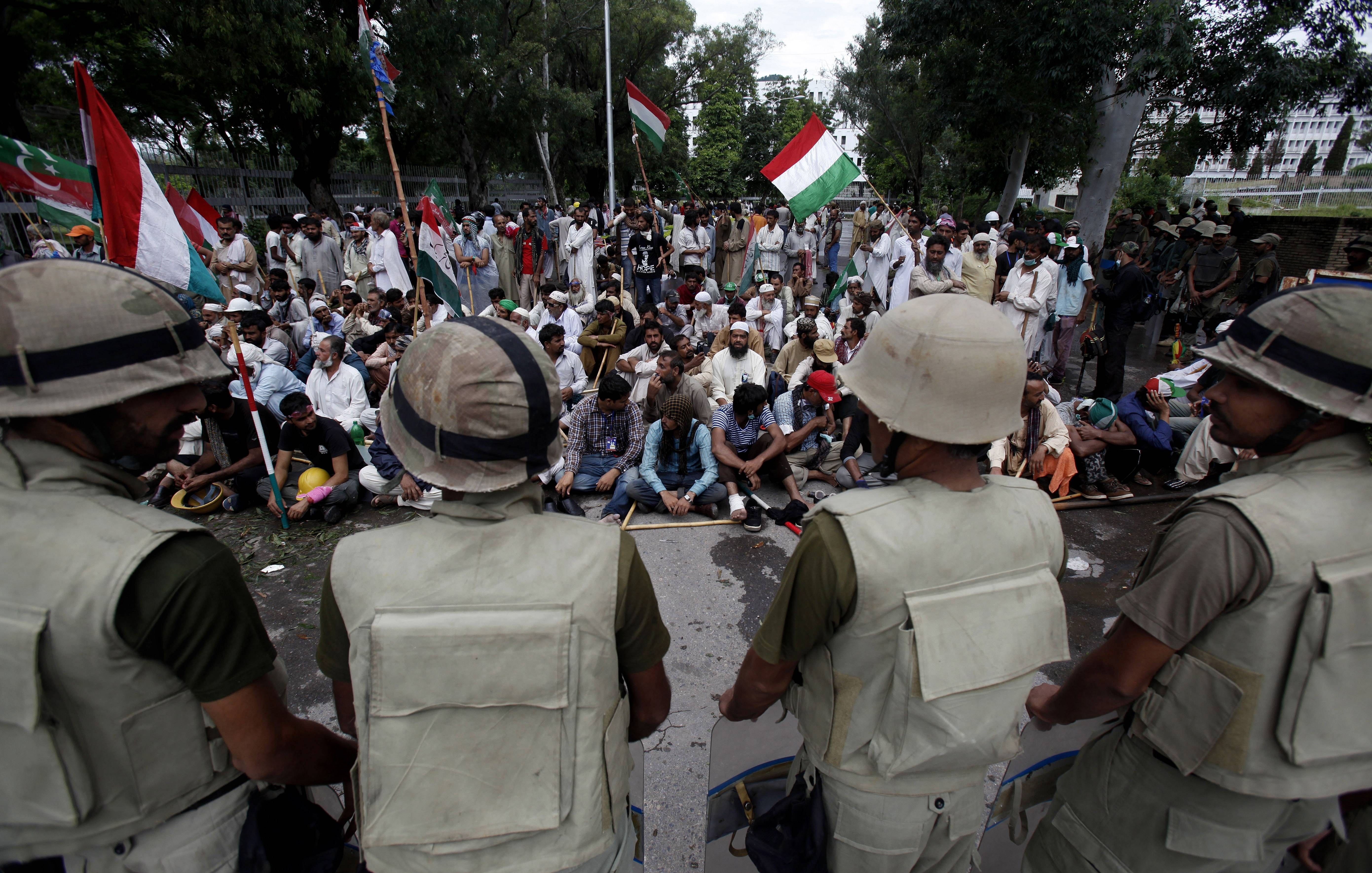 Pakistani troops stand guard as supporters of anti-government Muslim cleric Tahir-ul-Qadri stage a sit in protest close to Prime Minister's home in Islamabad Monday.
