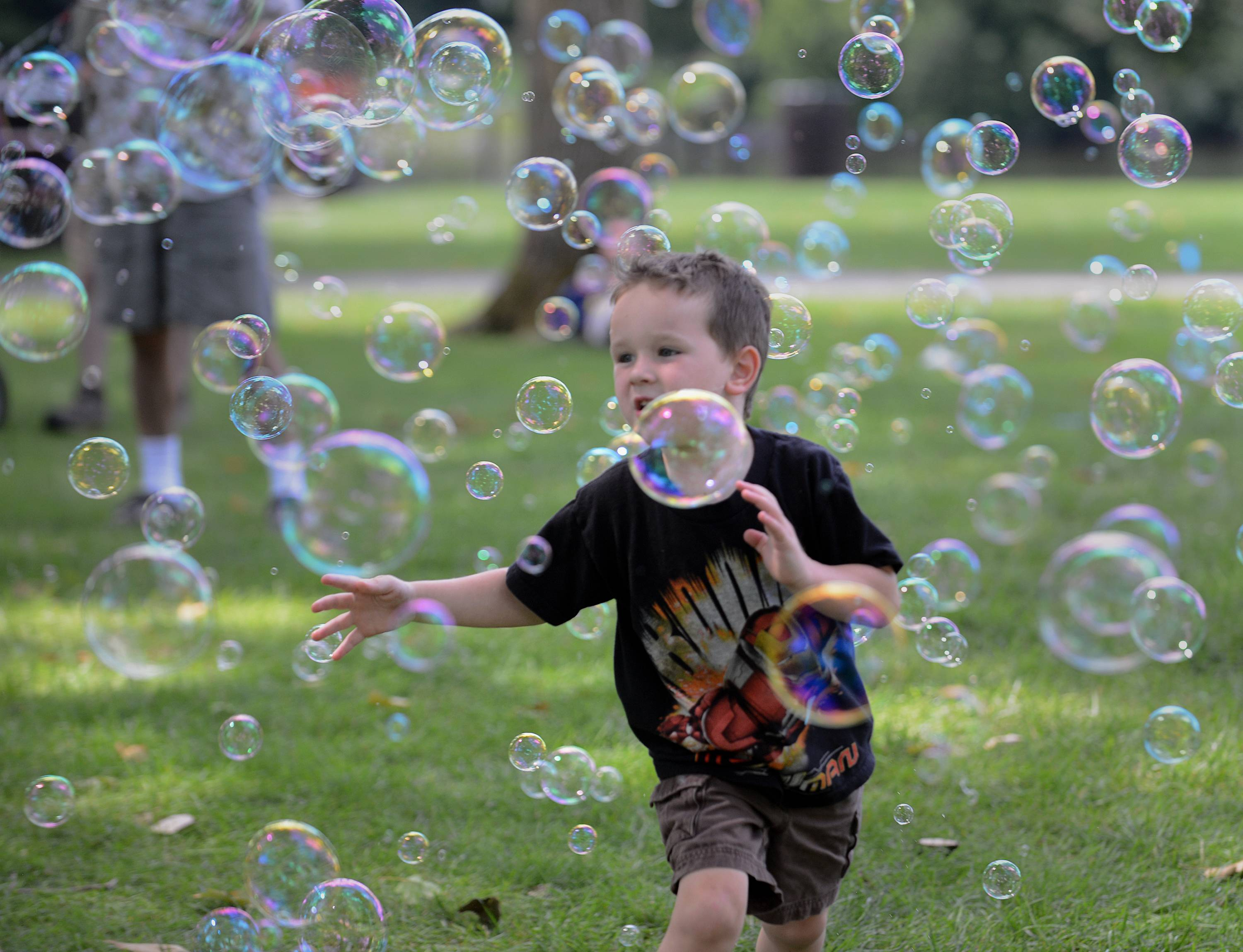 Caleb Talley, 4, of Crystal Lake chases bubbles Monday afternoon at the Fox Valley Folk Festival in Geneva. Ben Jimenez of Evanston, in the background, provided the bubbles.