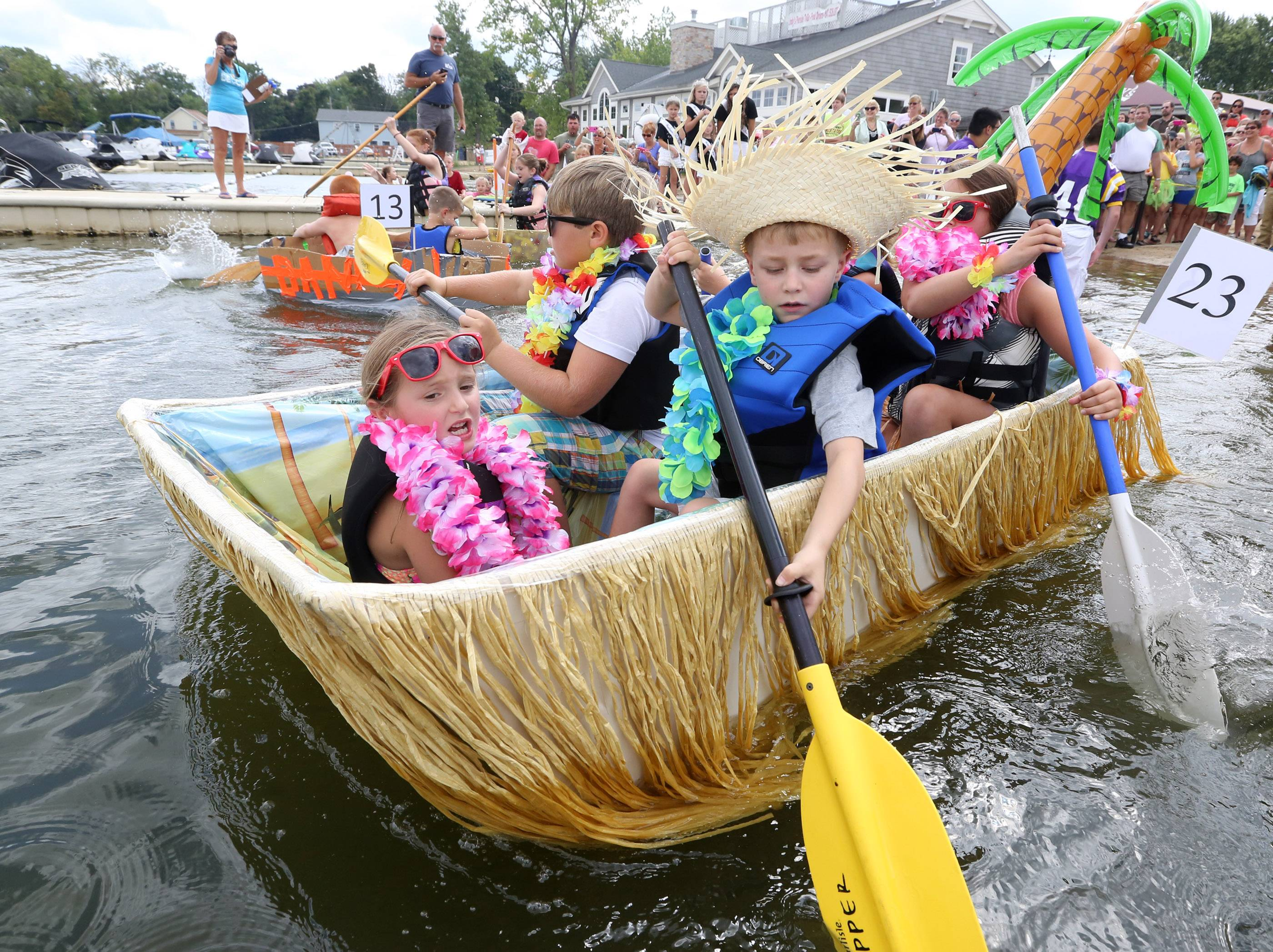 Maia Cordova, 7, of Wauconda, front, captains the boat as Austin Miller, 7, of Grayslake, left, front row of the boat, Max Testa, 9, of Cary, and Laindy Cordova, 7, back row right, paddle the boat to first place in the children's division of the 13th Annual Labor Day Cardboard Boat Races at Lindy's Landing on Saturday in Wauconda. Not shown in photograph in the boat is Sophia Testa, 11, of Cary.