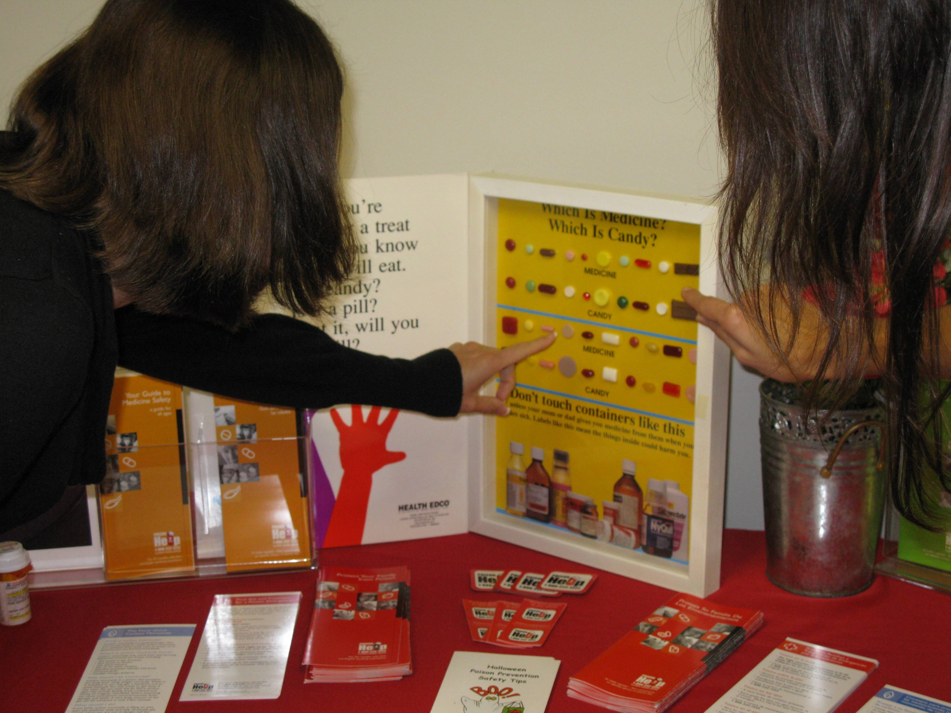 Children learn about medication safety from an Illinois Poison Center display. Call the free hotline at (800) 222-1222 if you are concerned about a possible poisoning.