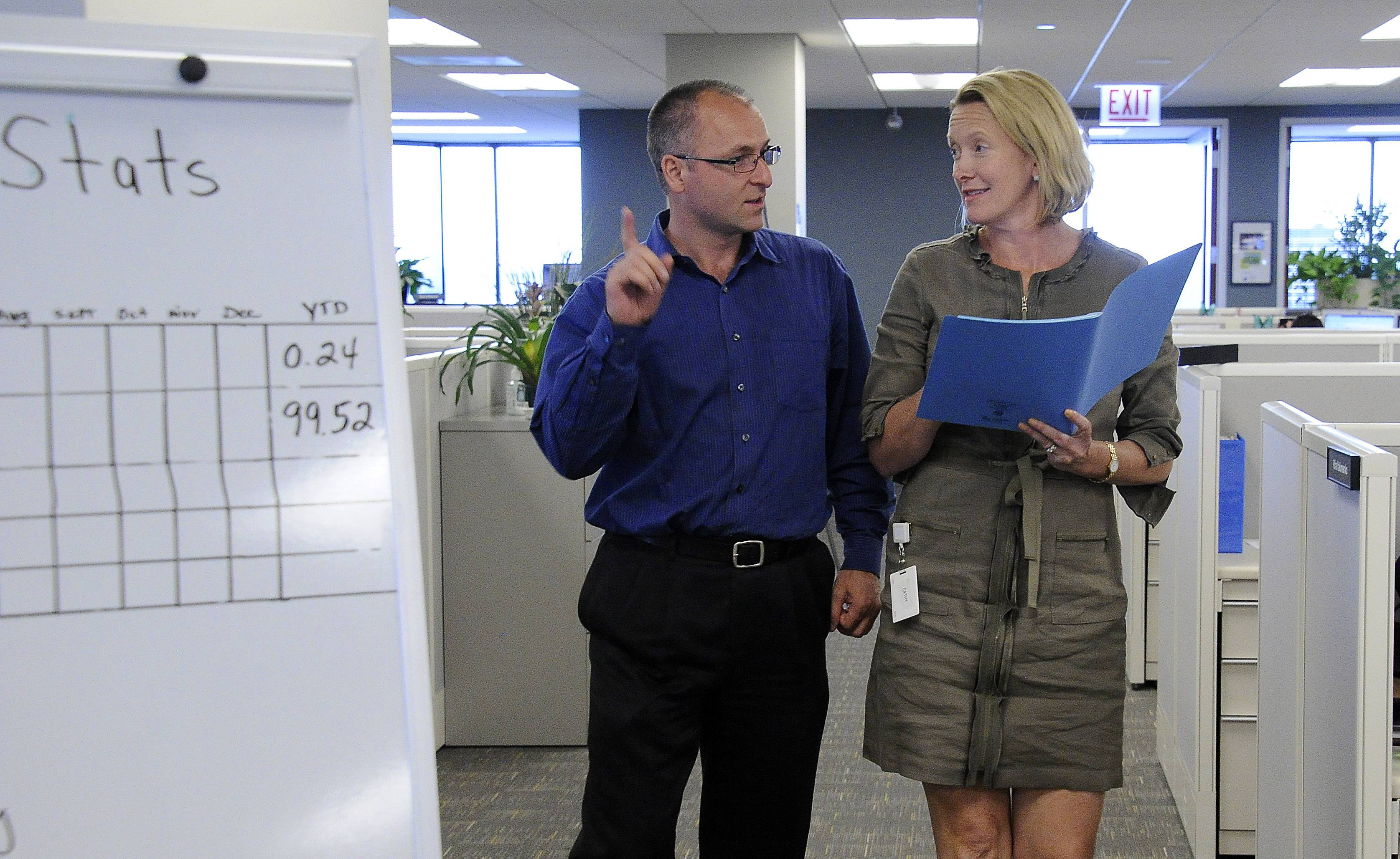 Cathy Kenworthy, president and CEO of Interactive Health, discusses the day events with Joe Szecsi, controller in their offices in Schaumburg.