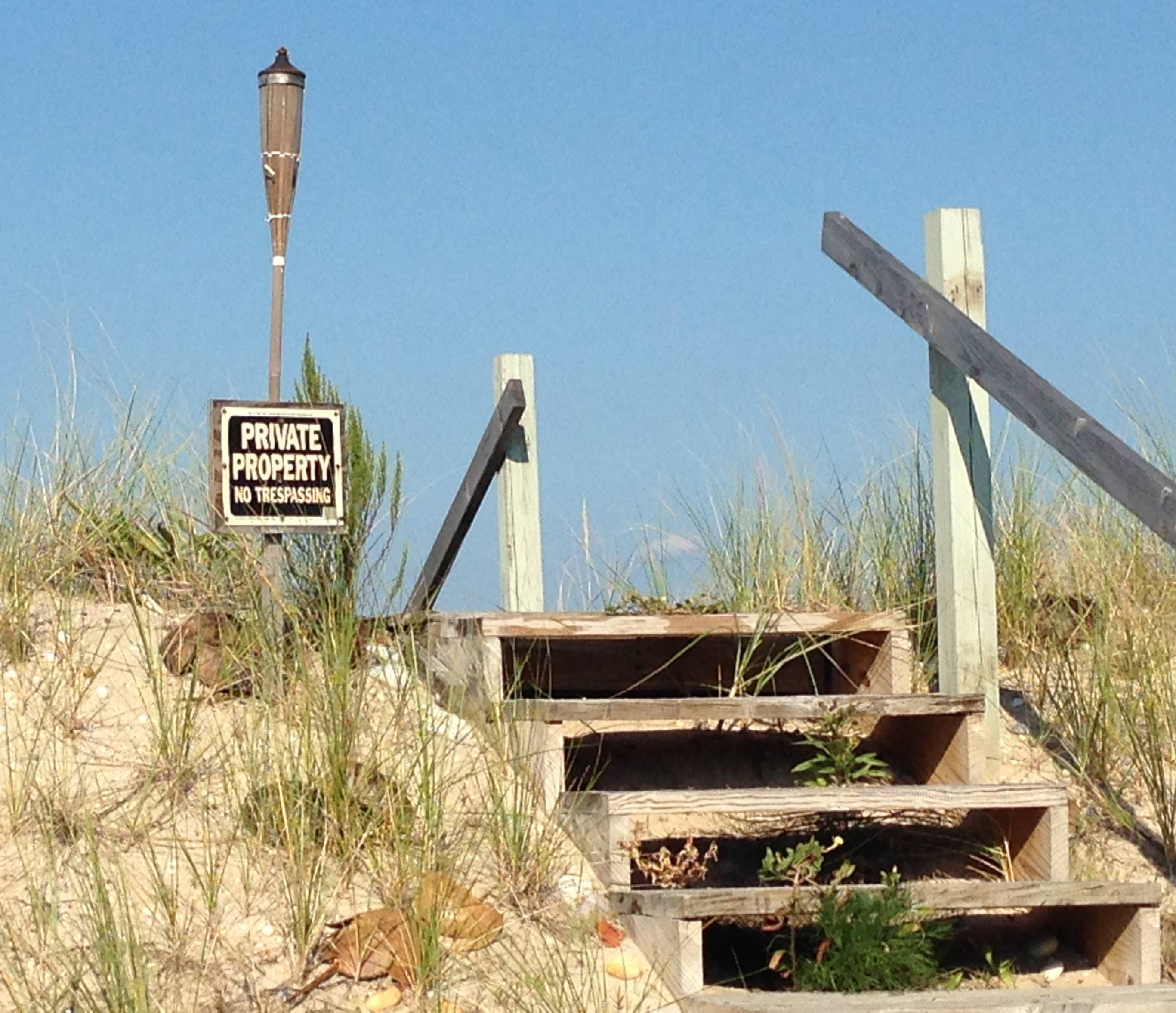 A private property sign in the village of Asharoken, N.Y., marks beachfront and stairs leading to the beach. Property owners without waterfront property in Asharoken can buy beach property for access to the water. Many owners have built boardwalks, walkways and other routes to the beach, which are often marked with private property signs.